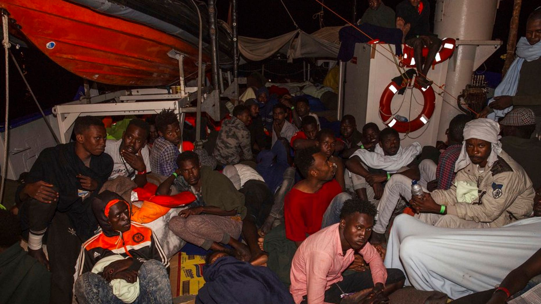 Rescued migrants sit in the search-and-rescue ship of German aid group Mission Lifeline as the boat remained stranded off Malta with 234 migrants aboard and no port at which to dock after both Italy and Malta refused to give authorization, early Monday, June 25; a deal has now been worked out