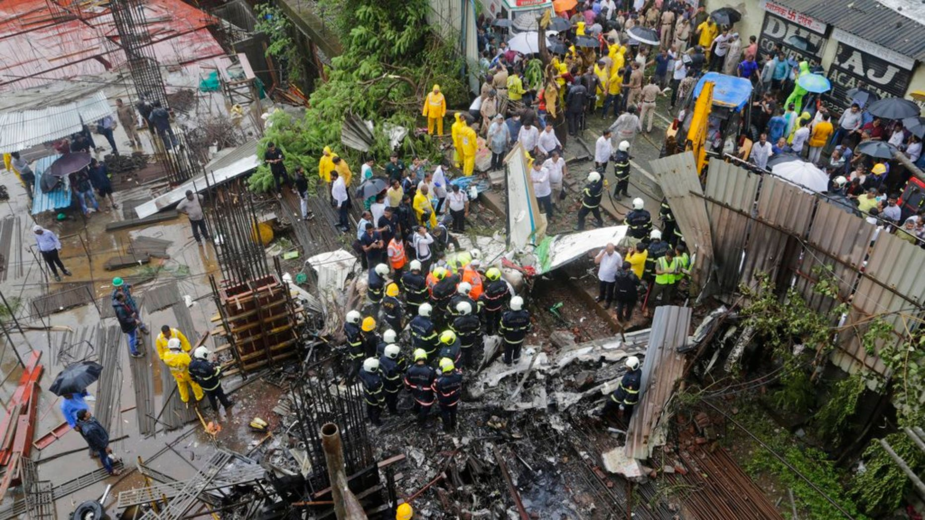 In this June 28, 2018 photo, rescuers stand amid the wreckage of a private chartered plane that crashed in Ghatkopar area, Mumbai, India.