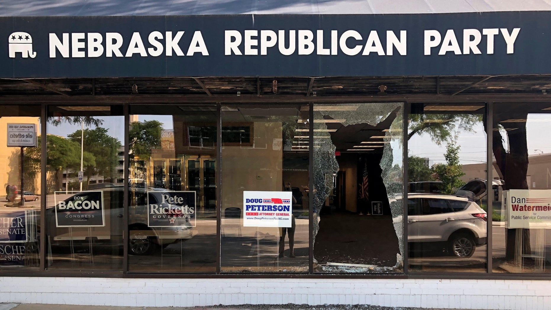 "A broken window greets passers-by outside the Nebraska Republican Party's office in Lincoln, Neb., on Tuesday, July 3, 2018. Vandals threw a brick through the window overnight and scrawled the words ""Abolish ICE"" on the sidewalk below it."