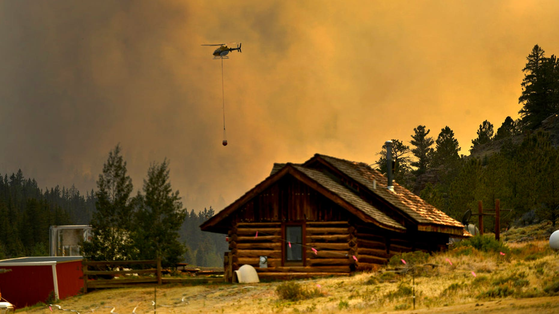 In this Monday, July 2, 2018 photo, a helicopter returns for water after making a water drop on a wildfire near Fairplay, Colorado.