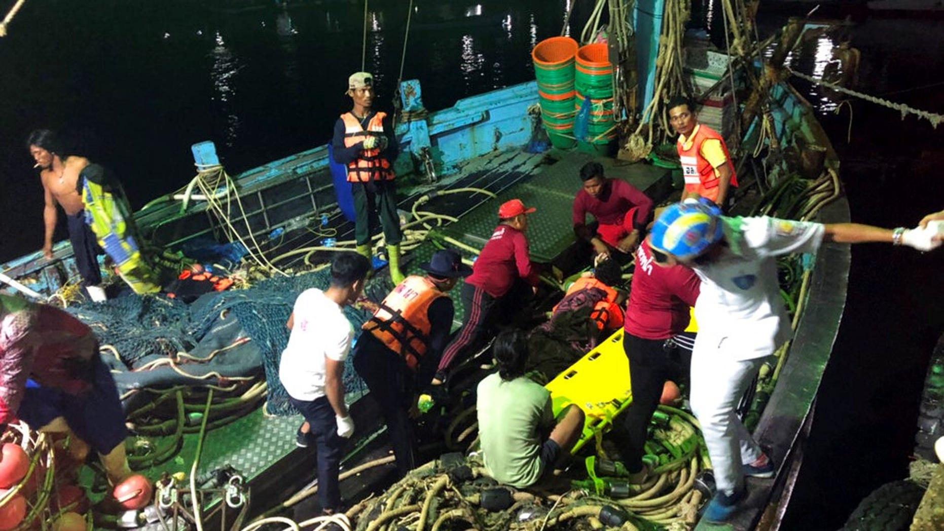 Rescued tourists from a boat that sank are helped onto a pier from a fishing boat Thursday, July 5, 2018, on the island of Phuket, southern Thailand.