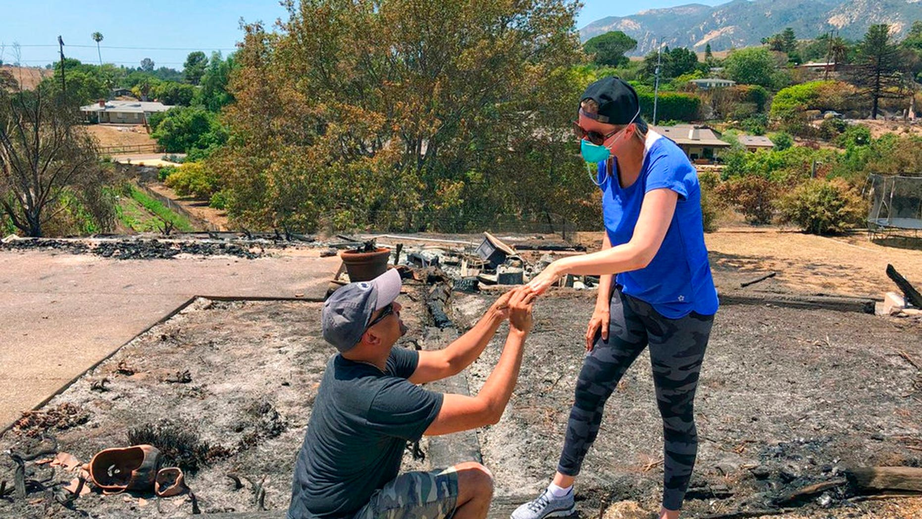 Ishu Rao gets down on one knee to return his wife's wedding ring to her next to the charred remains of their Goleta, Calif. home.