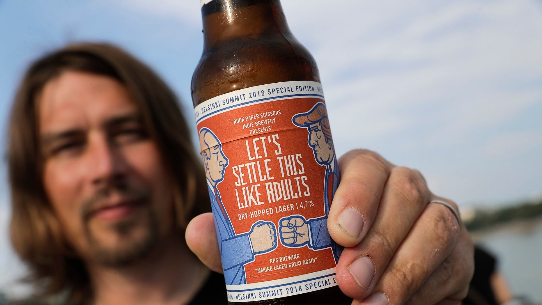 "Samuli Huuhtanen, CEO of Finnish brewery Rock Paper Scissors, displays a bottle of ""Let's Settle this Like Adults,"" a beer inspired by Monday's scheduled Trump-Putin summit."