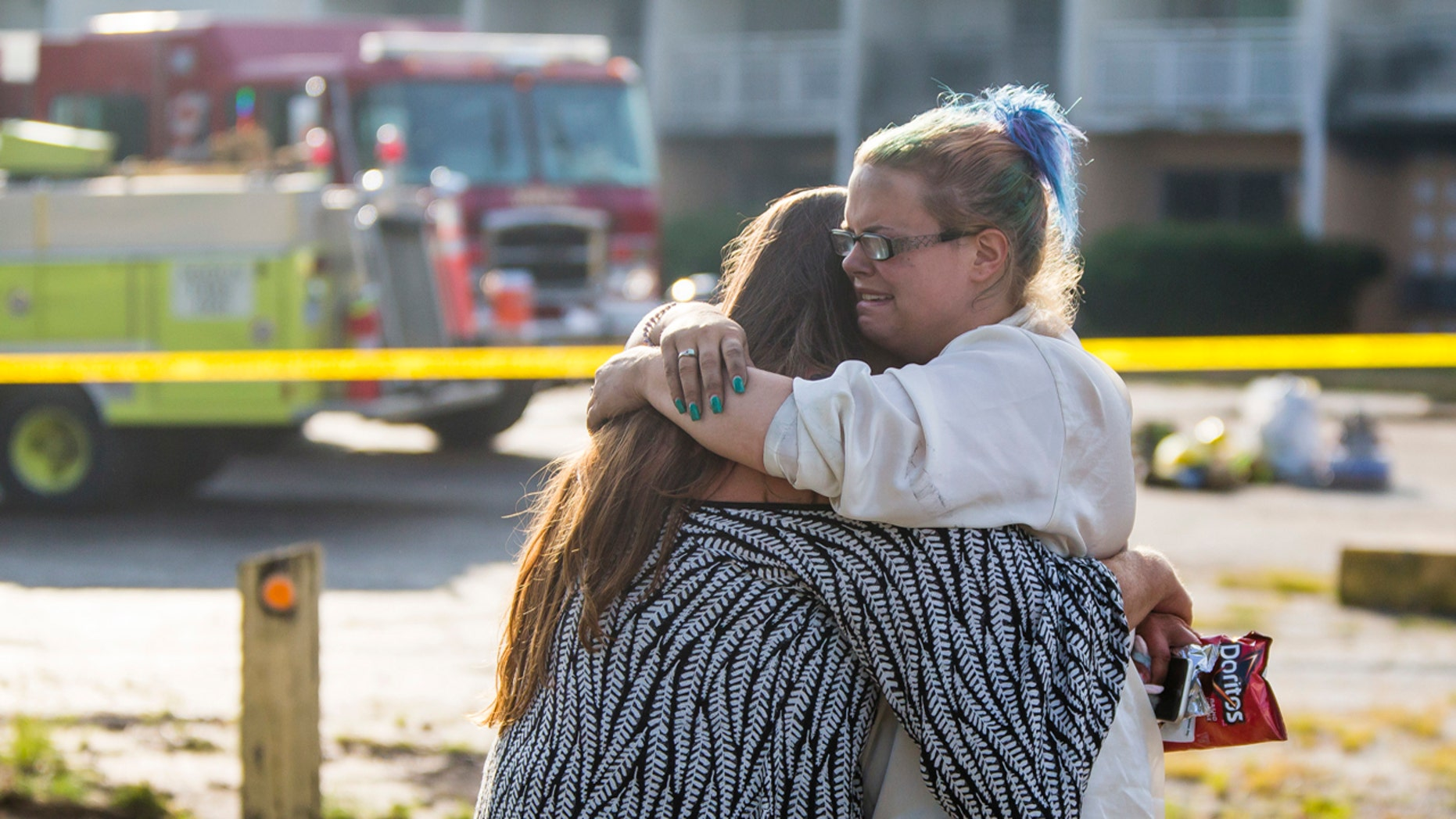 Hotel residents Cassundra Clements, left, and Sarah Sanders comfort one another after a fire at the Cosmo Extended Stay Motel in Sodus Township, Mich., July 28, 2018.
