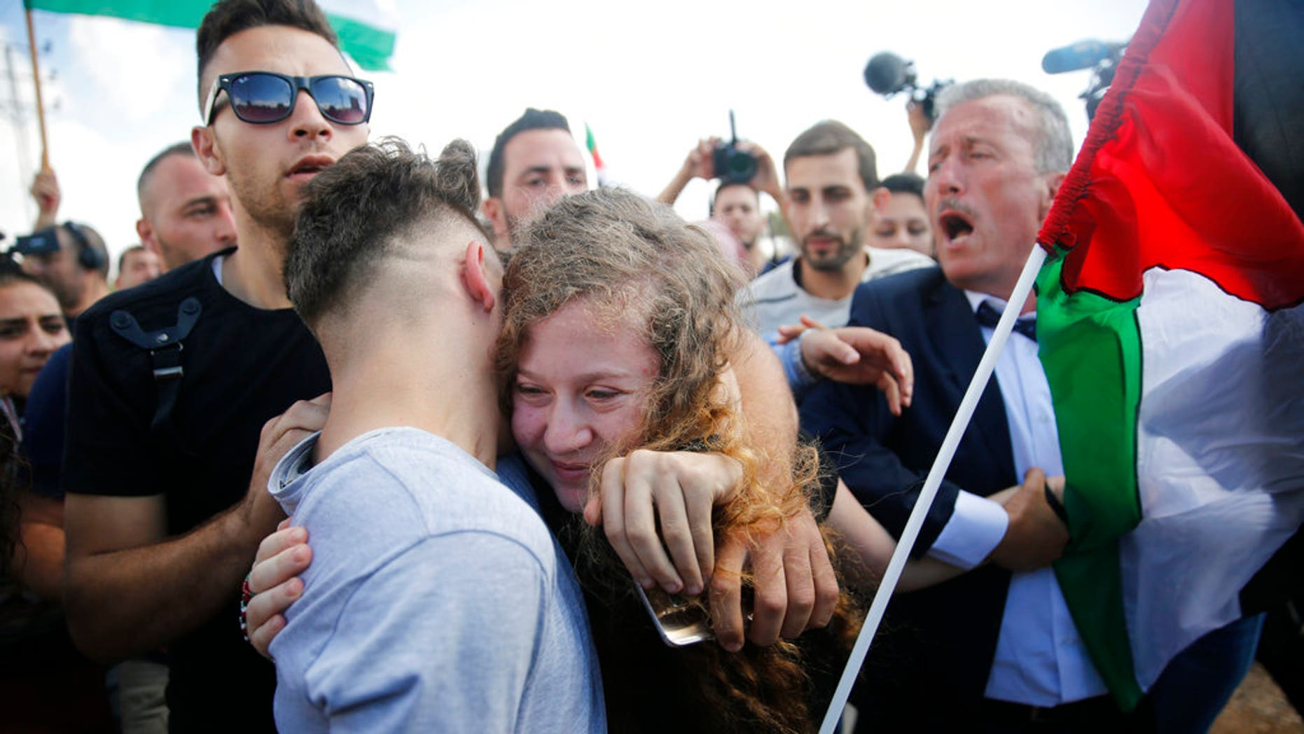 Ahed Tamimi is hugged after she was released by the Israel army in her village of Nebi Saleh in the West Bank Sunday, July 29, 2018. Palestinian protest icon Ahed Tamimi returned home to a hero's welcome in her West Bank village on Sunday after Israel released the 17-year-old from prison at the end of her eight-month sentence for slapping and kicking Israeli soldiers.