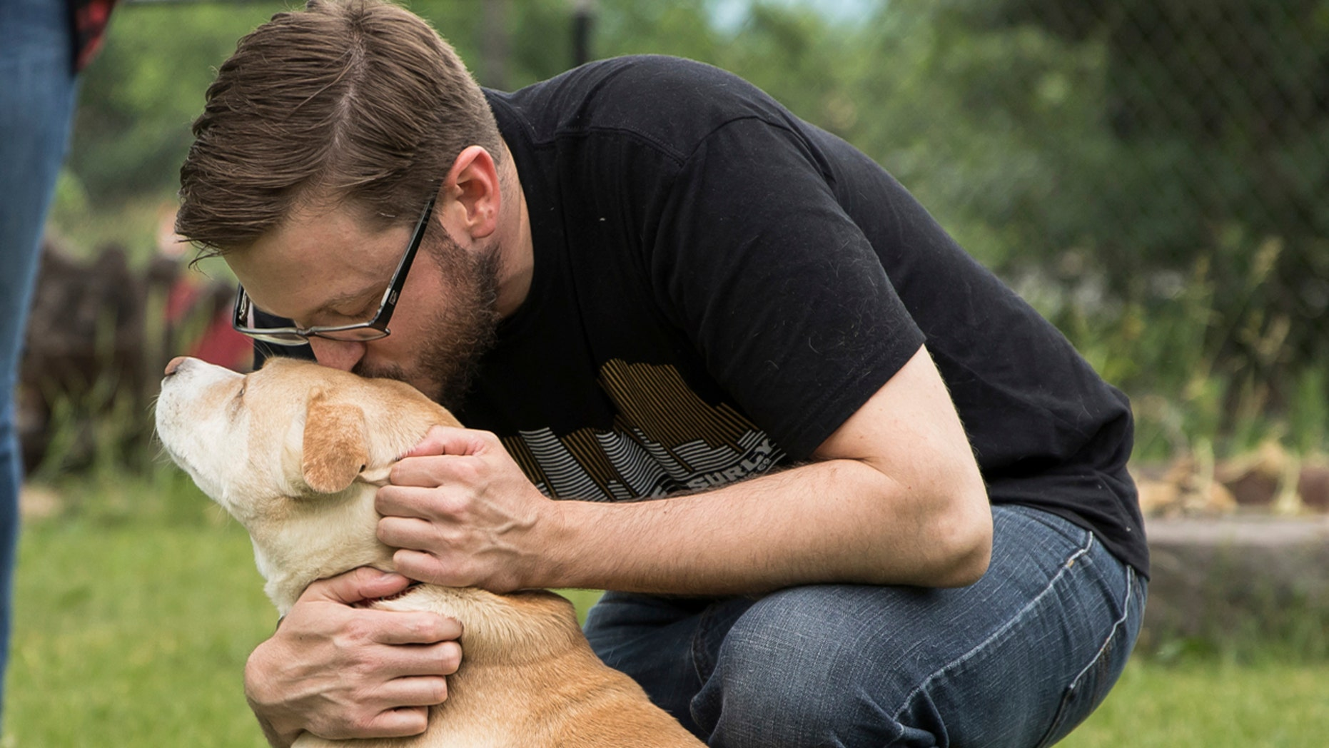 Mike Liay kisses his dog Archie's head in Minneapolis, June 18, 2018. Airlines and cruise ships are tightening restrictions on emotional support animals (ESAs).