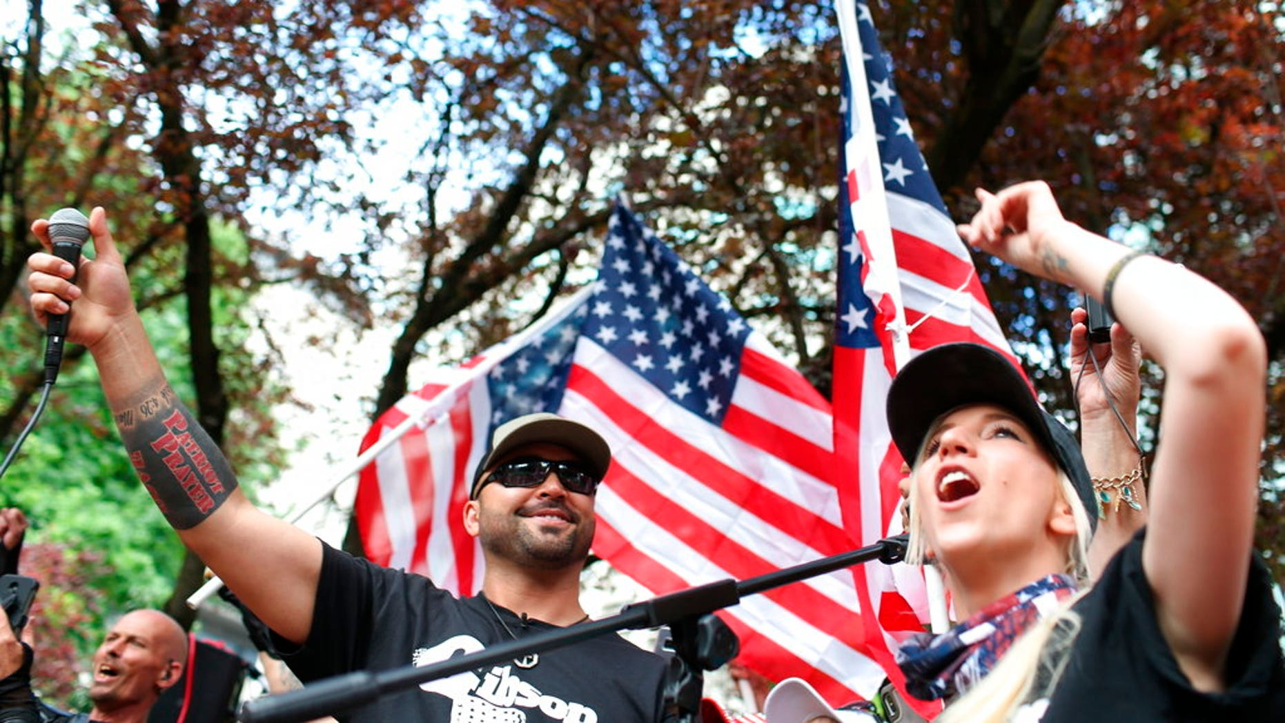 FILE--In this June 30, 2018, file photo, Joey Gibson, left, leader of Patriot Prayer, heads the group's rally in Portland, Ore. Portland is bracing for what could be another round of violent clashes Saturday, Aug. 4, 2018, between a right-wing group holding a rally here and self-described anti-fascist counter-protesters who have pledged to keep Patriot Prayer and other affiliated groups out of this ultra-liberal city. (Mark Graves/The Oregonian via AP, file)