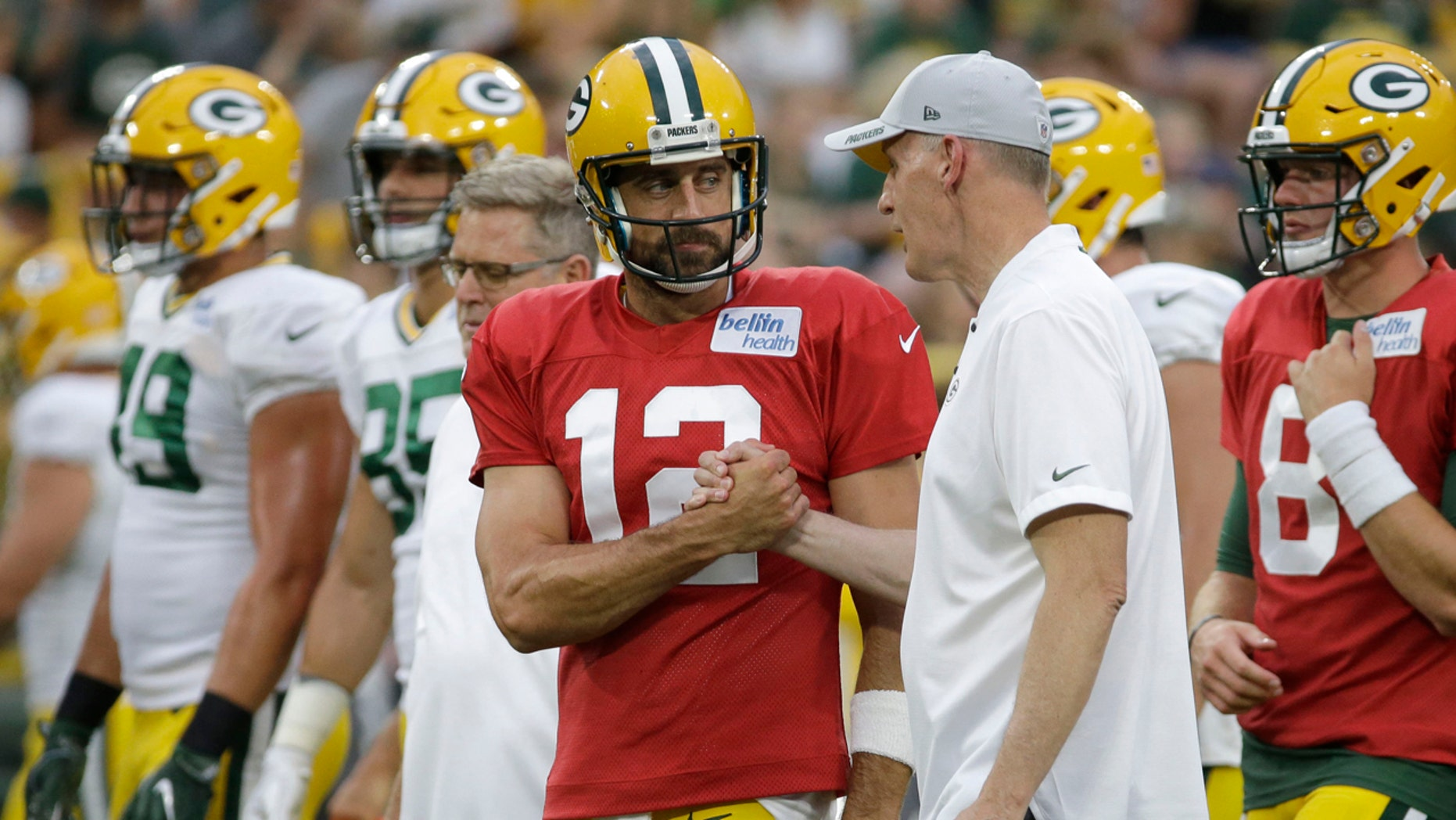 Green Bay Packers quarterback Aaron Rodgers shakes hands with new offensive coordinator Joe Philbin during the NFL football team's Family Night practice Saturday, Aug. 4, 2018 in Green Bay, Wis.