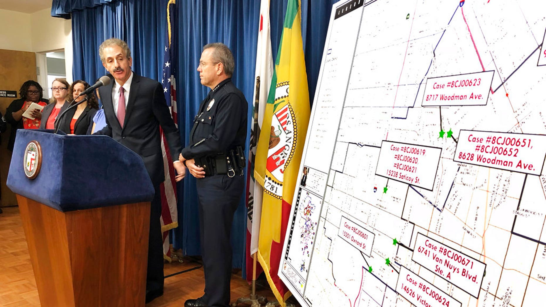 Los Angeles City Attorney Mike Feuer, at podium, and police Chief Michel Moore announce that prosecutors have charged more than 500 people with misdemeanors for illegal marijuana operations, at a news conference in Los Angeles, Sept. 7, 2018.
