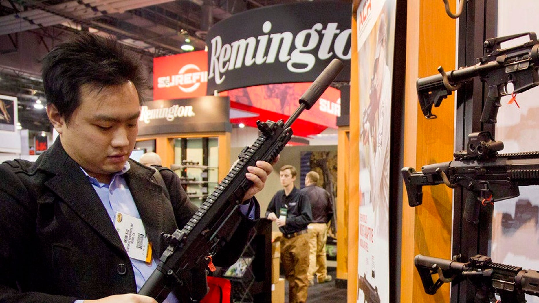 FILE- In this Jan. 15, 2013, file photo, accessories manufacturer Kevin Kao, of Irvine, Calif., examines a military grade Remington Adaptive Combat Rifle at the 35th annual SHOT Show in Las Vegas. A U.S. judge has struck down a nearly century-old California law that banned gun shops from advertising handguns on their premises. Judge Troy Nunley in Sacramento ruled Tuesday, Sept. 11, 2018, that the law violated the First Amendment. Nunley said the state failed to show that enforcing the law would prevent violence or suicides. The ruling came in a lawsuit filed in 2014 by several gun dealers who were fined by the state for handgun ads. The 1923 law banned any handgun ads at gun shops that were visible from outside the store. (AP Photo/Julie Jacobson, File)
