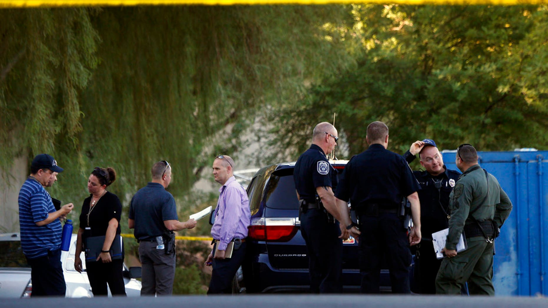 In this Sept. 11, 2018 photo, North Las Vegas and Las Vegas Metro Police investigate a fatal shooting near a baseball field at a North Las Vegas high school.