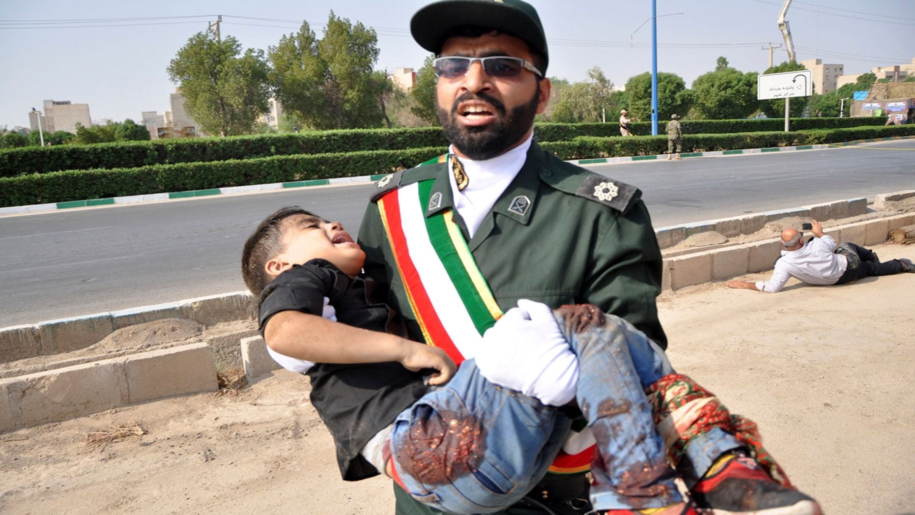 A Revolutionary Guard member carries a wounded boy after a shooting during a military parade marking the 38th anniversary of Iraq's 1980 invasion of Iran, in the southwestern city of Ahvaz, Iran, Saturday, Sept. 22, 2018.