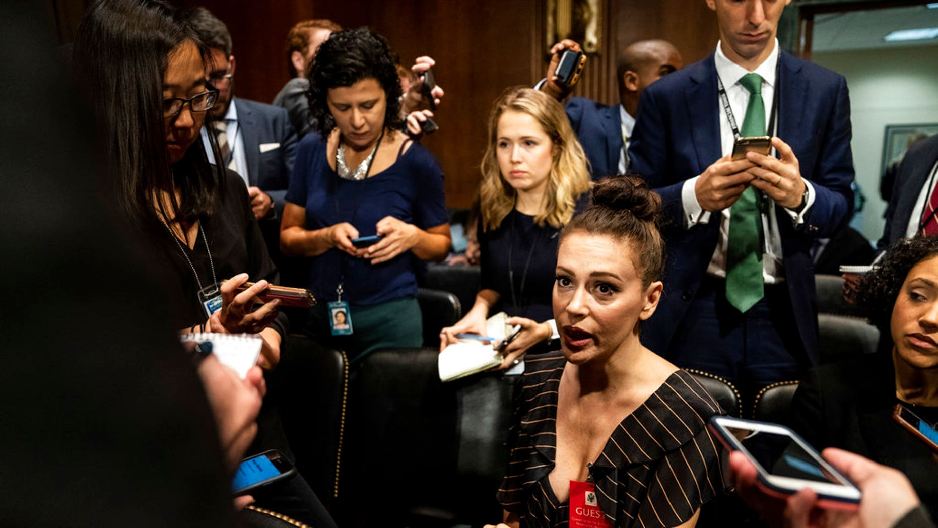 Actress Alyssa Milano is seen before a Senate Judiciary Committee hearing, Thursday, Sept. 27, 2018 on Capitol Hill in Washington with Christine Blasey Ford and Supreme Court nominee Brett Kavanaugh. (Erin Schaff/The New York Times via AP, Pool)