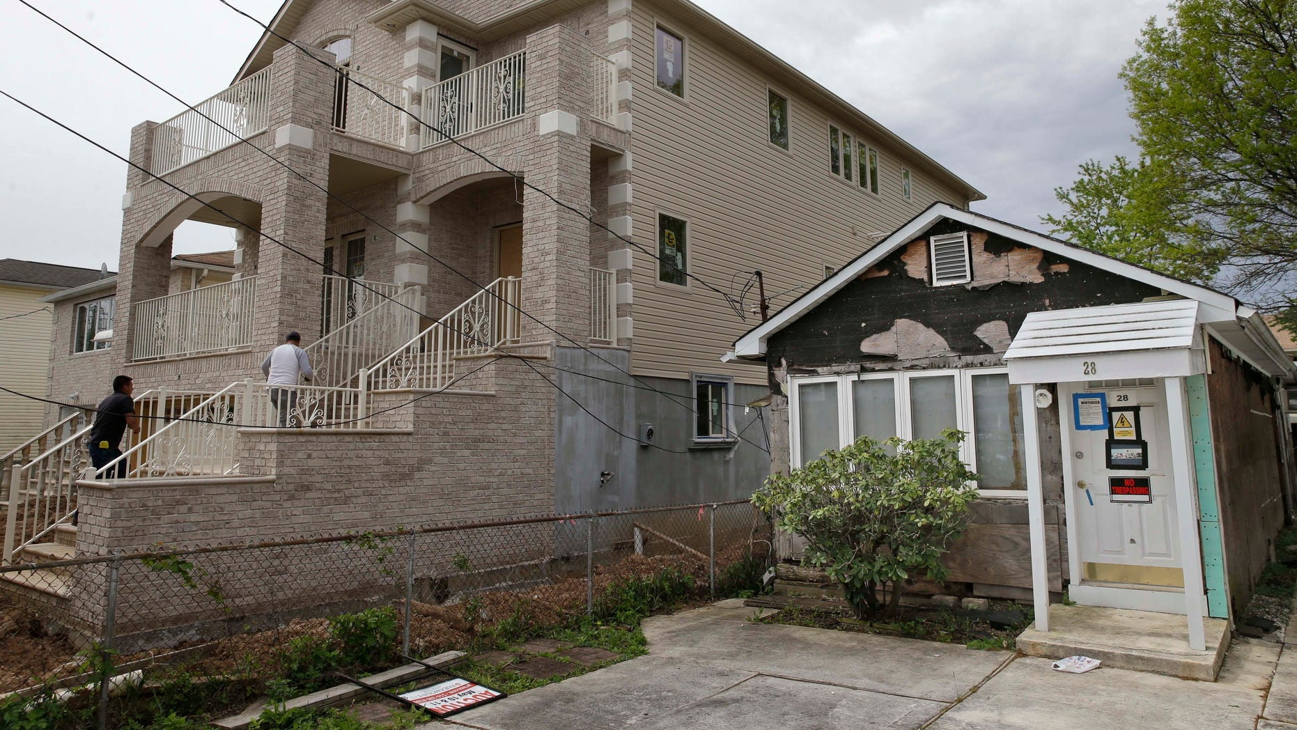 A house up for auction, right, sits next to a rebuilt and raised home in the New Dorp Beach section of New York's Staten Island.