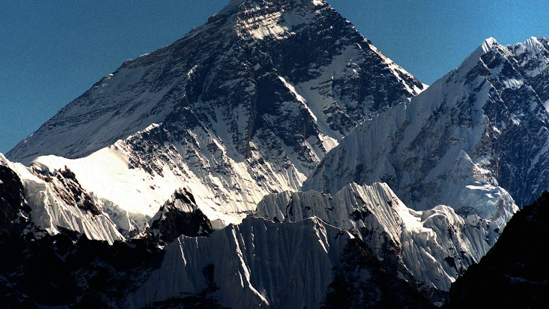 FILE - In this October 1996 file photo, Mount Everest is seen from peak Gokyo Ri in Nepal. Chinese state-run mobile news site The Paper reported Wednesday, May 11, 2016, that workers had removed the signatures, dates, doodles and messages left by scores of visitors on two granite tablets on the Chinese side of Mount Everest's northern base camp and plan to name and shame future defilers.(AP Photo/Hans Edinger)
