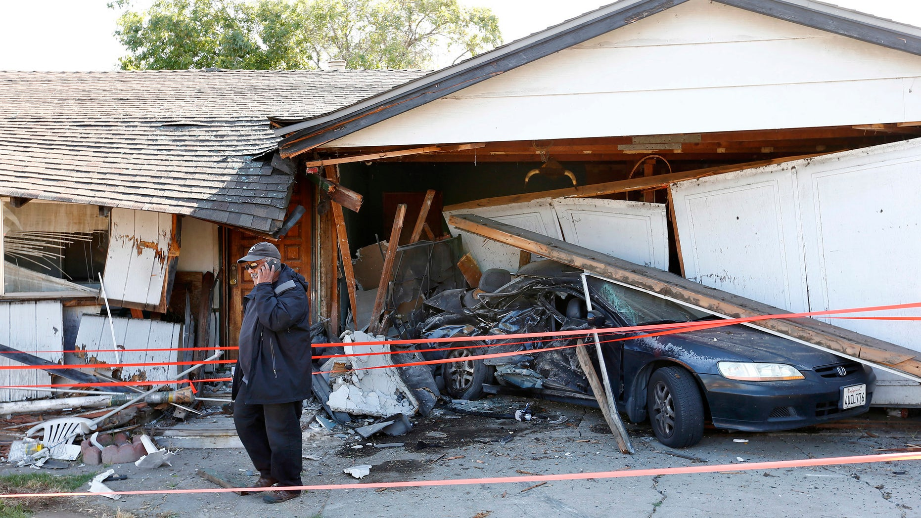 Ray Minter talks on the phone after a truck ran into his home near Interstate 680 in San Jose Tuesday.