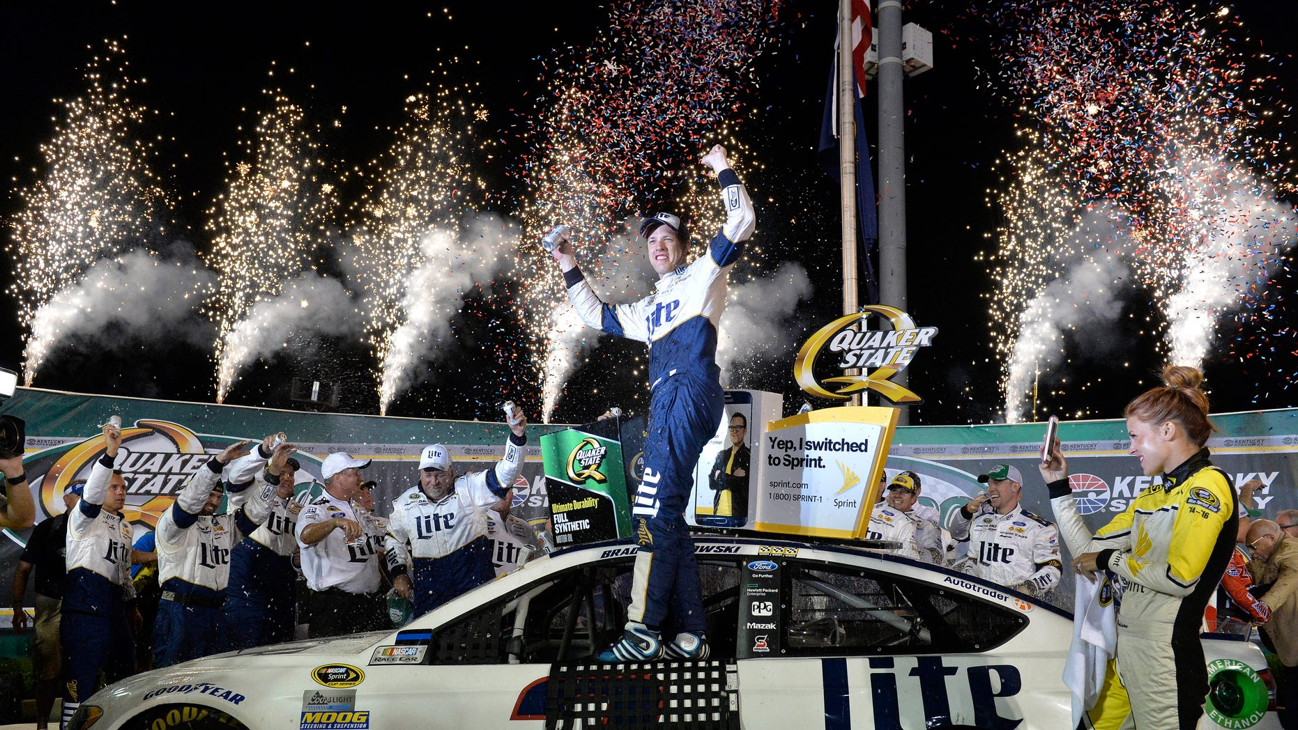 Brad Keselowski stands on his car in Victory Lane after his win in the NASCAR Sprint Cup Series auto race at Kentucky Speedway, Saturday, July 9, 2016 in Sparta, Ky. (AP Photo/Timothy D. Easley)