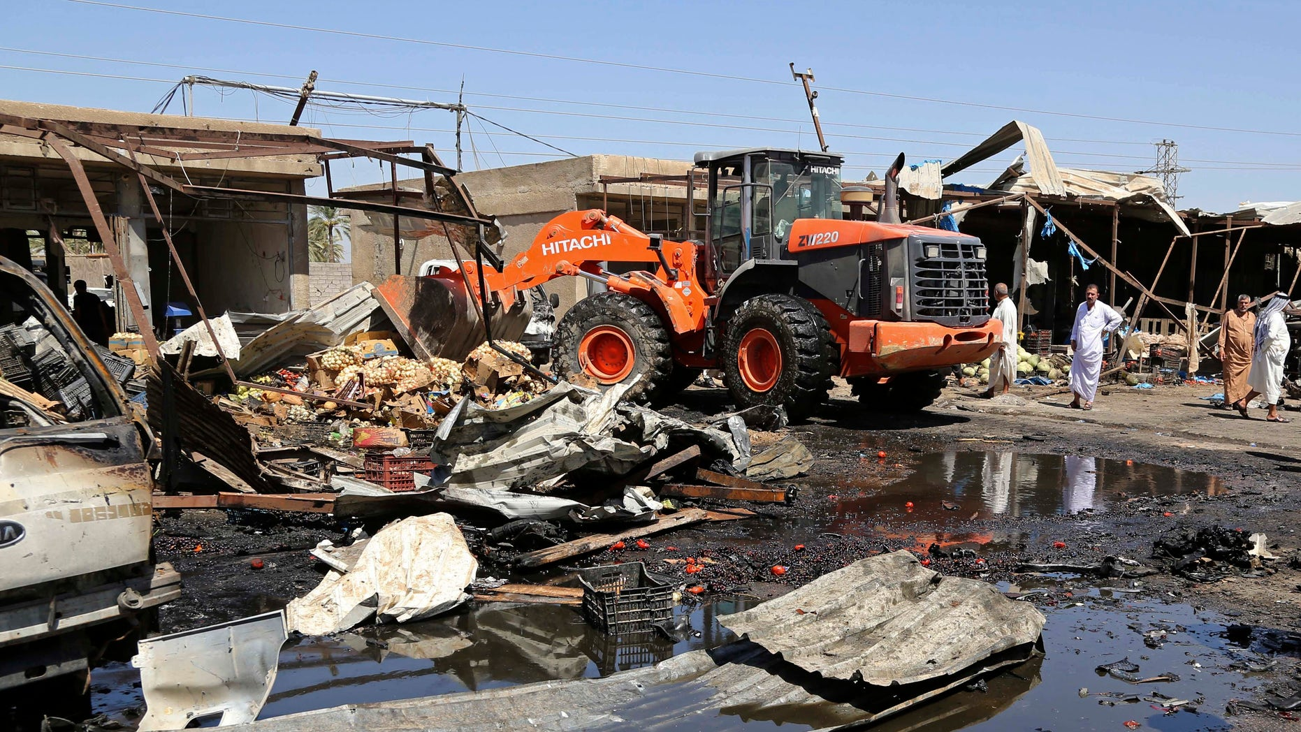 A bulldozer clears the scene of the suicide car bombing.