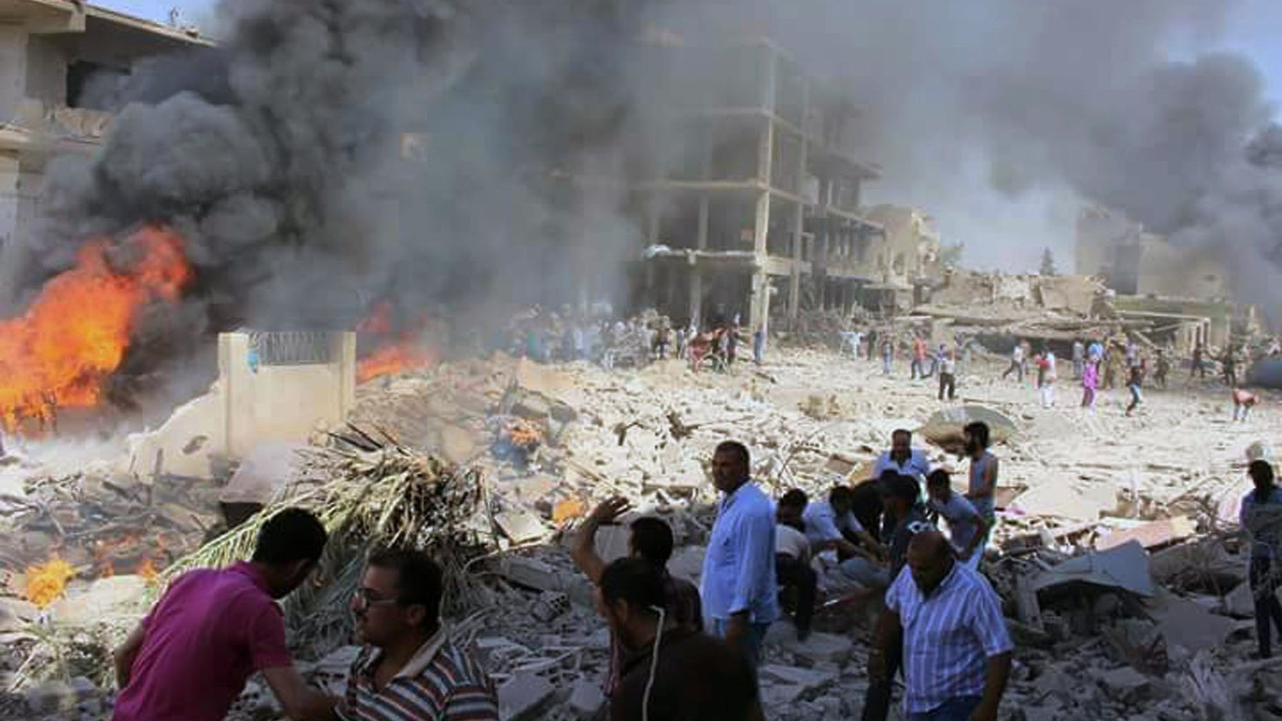 Syrians gather at the scene where twin bombings struck Kurdish town of Qamishli, Syria.