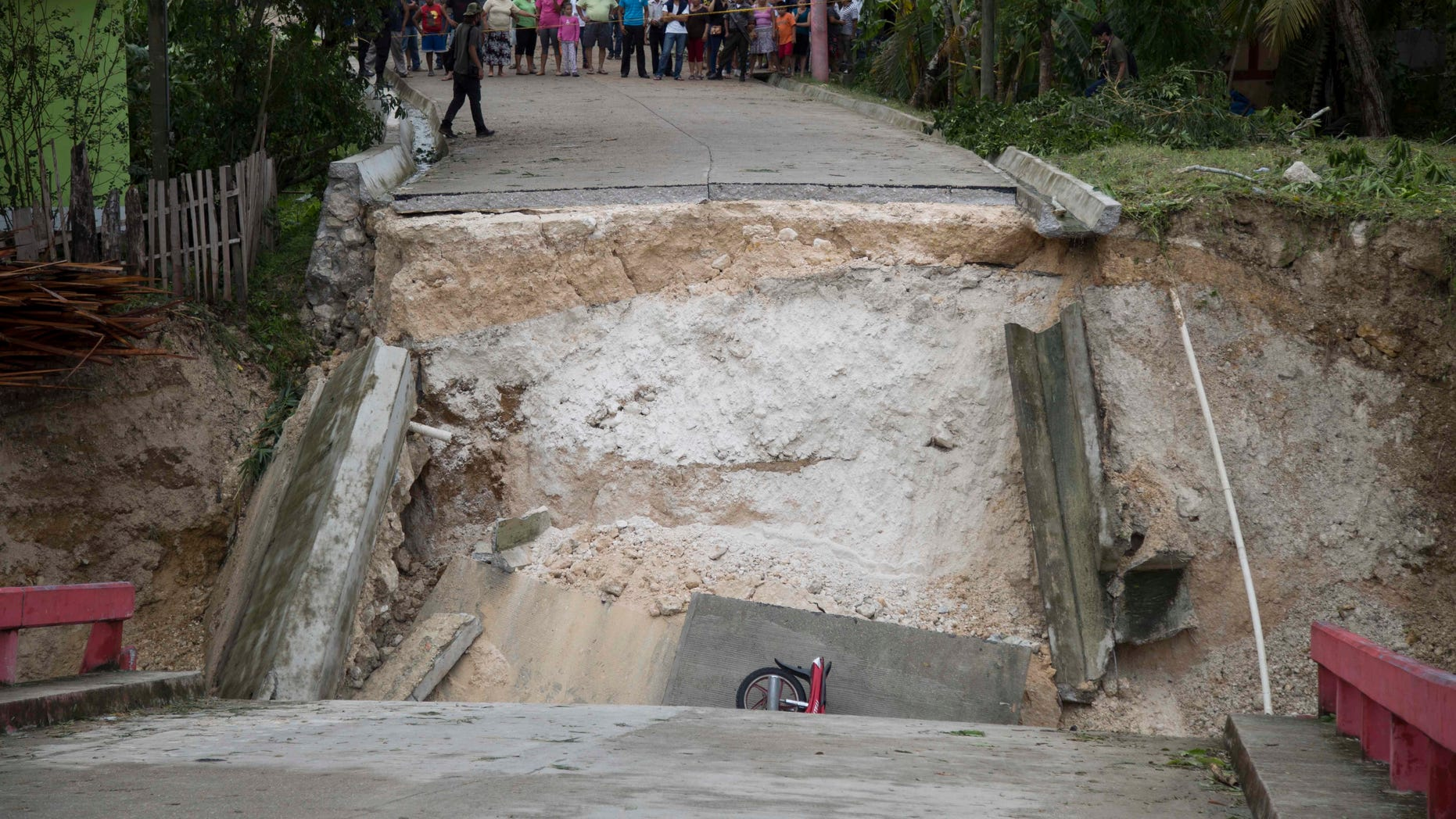 A motorcycle lies in the debris of a collapsed bridge brought down by Hurricane Earl in the Arroyito neighborhood, in Melchor de Mencos, Guatemala on August 4.