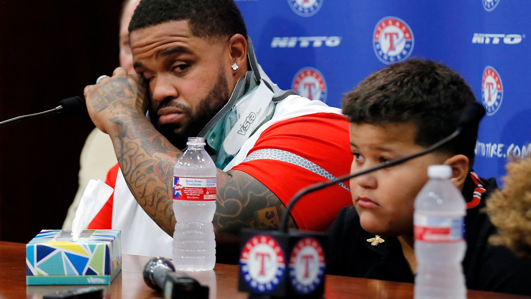 The Texas Rangers' Prince Fielder wipes his eyes as he sits by his son Haven during a news conference.
