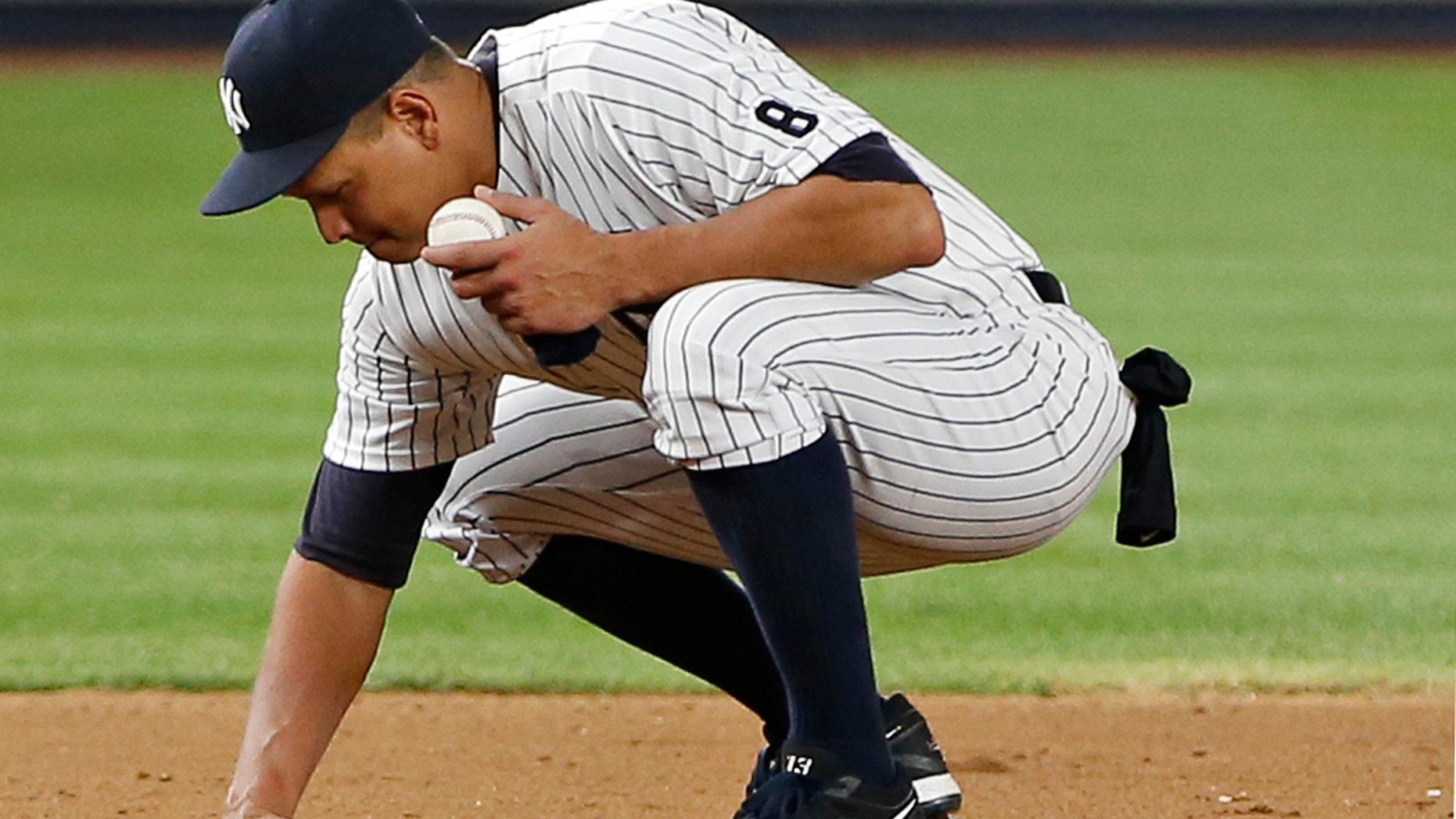 Alex Rodriguez gathers dirt from the field near third base in his final game as a Yankee.