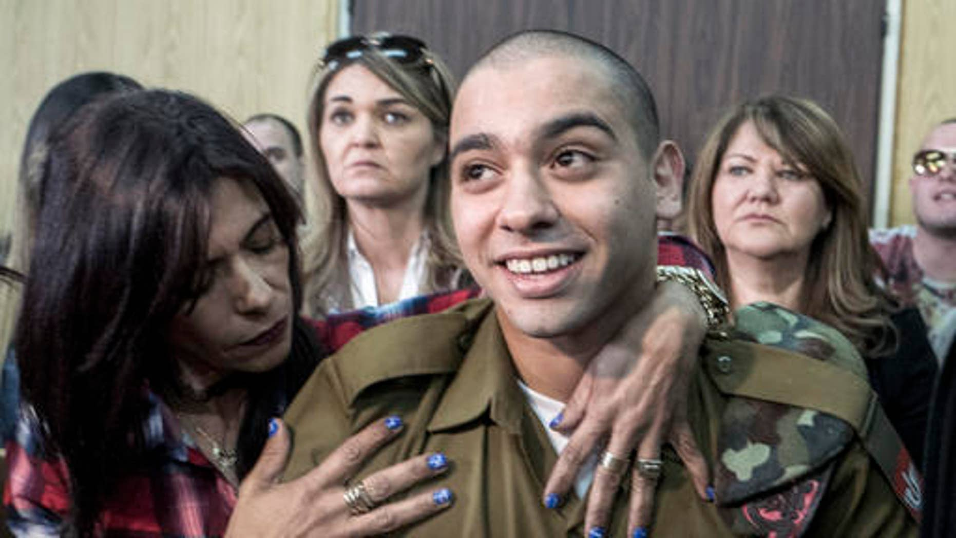 Elor Azaria embraced by his mother at the start of his sentencing hearing.