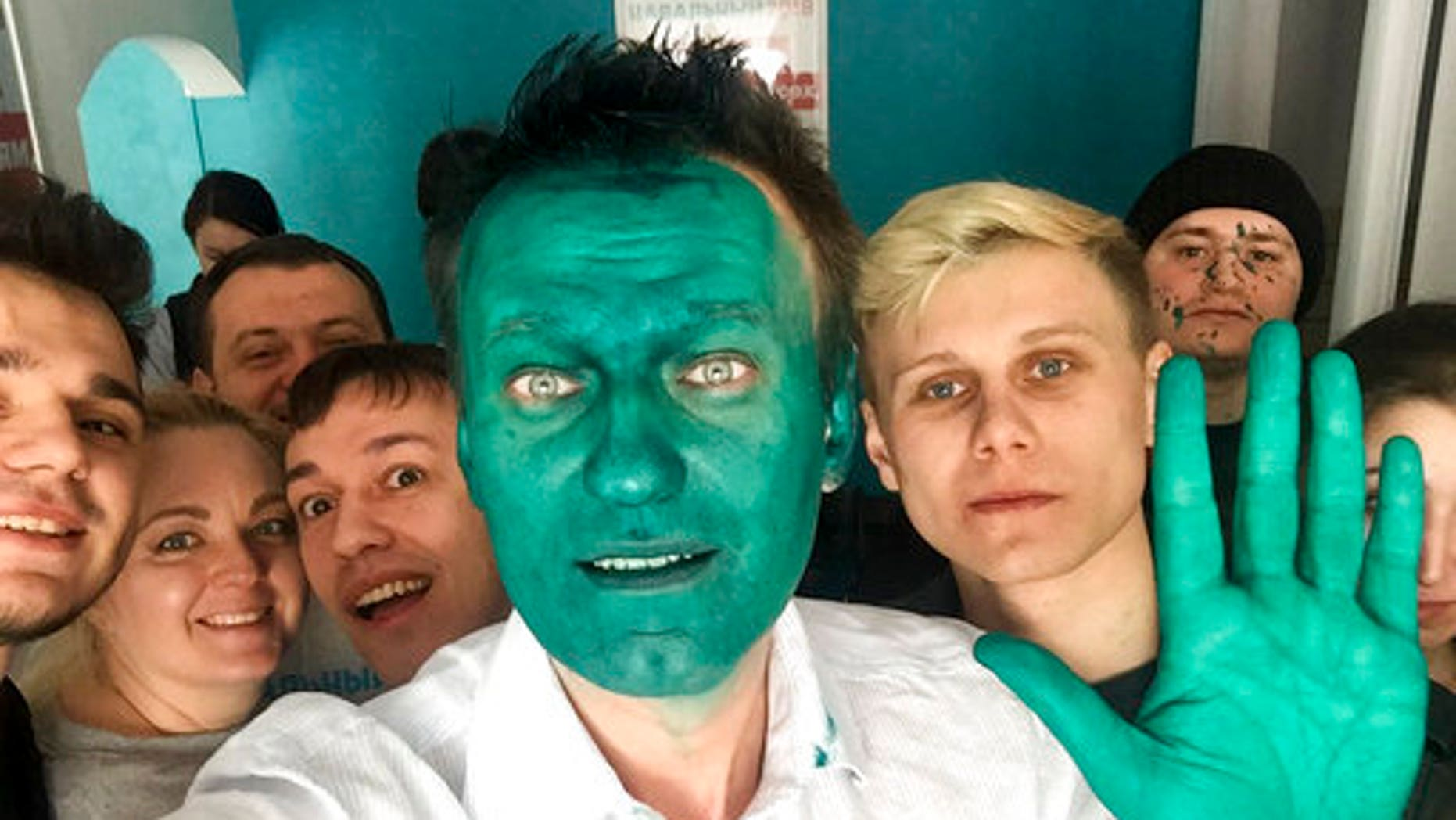 Russian opposition leader Alexei Navalny takes a selfie with supporters after he said an unknown attacker sprayed a bright green antiseptic on his face.
