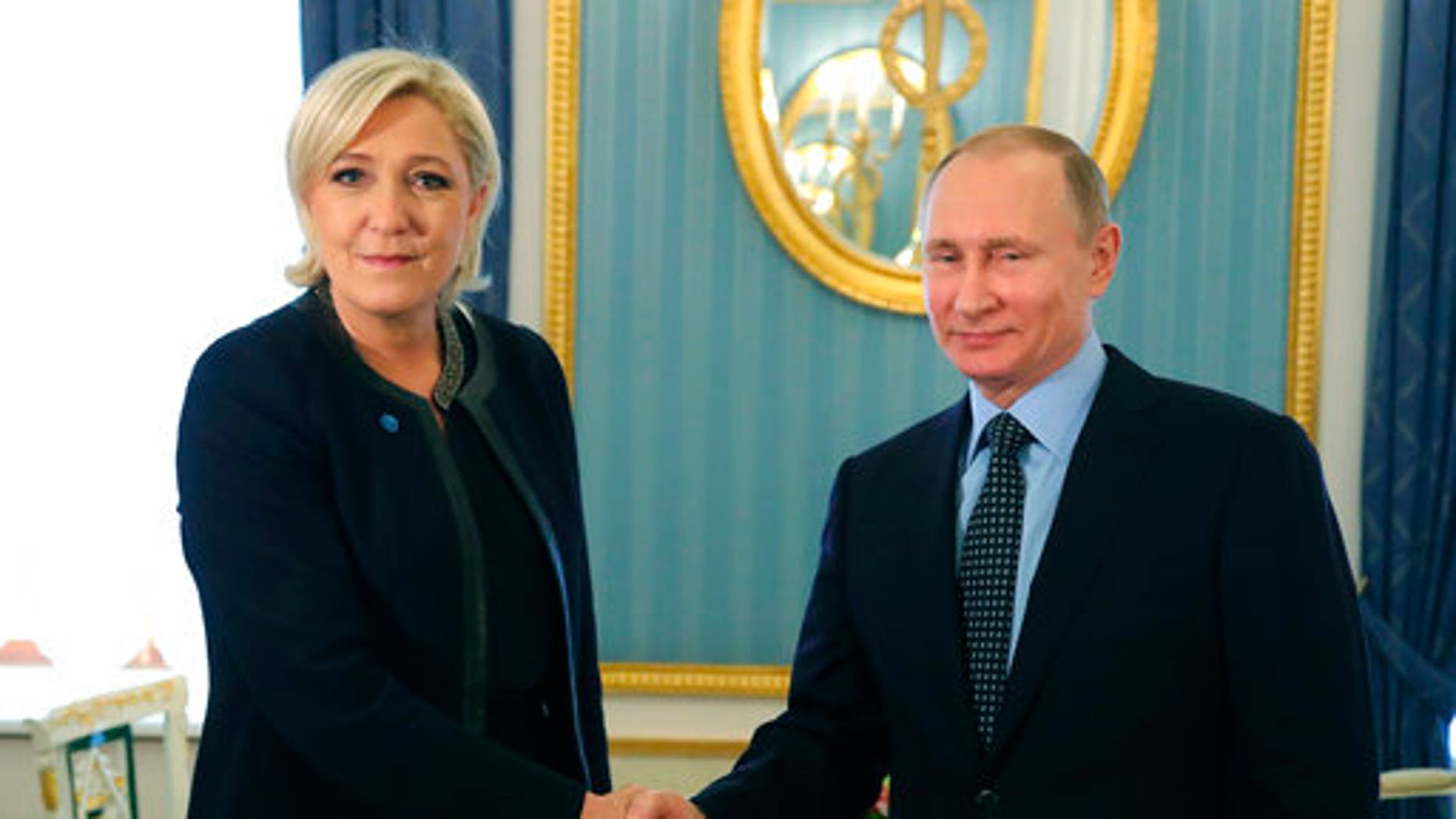 Russian President Vladimir Putin, right, shakes hands with French presidential candidate Marine Le Pen at the Kremlin.