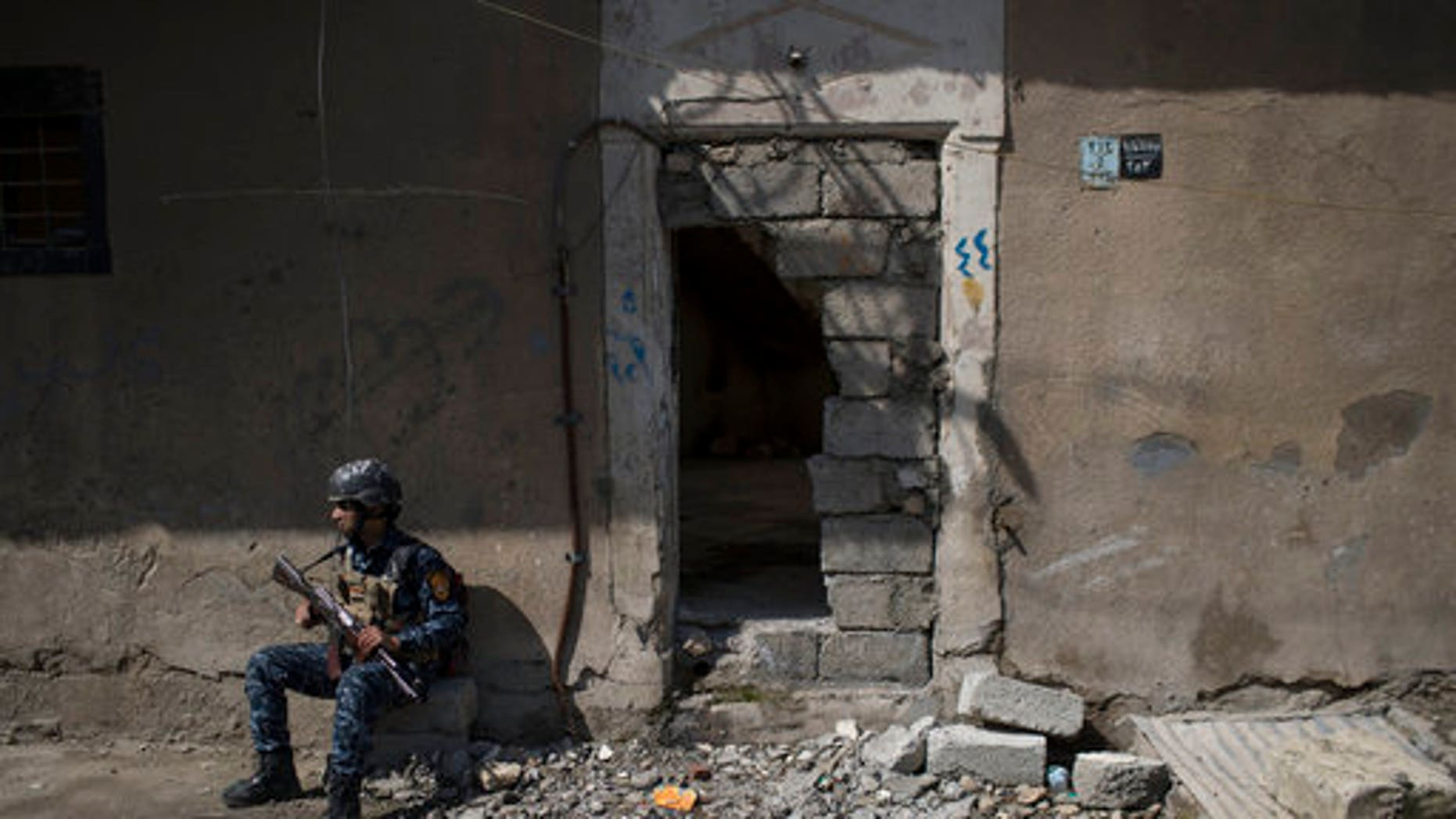 A federal policeman takes a break from inspecting houses during fighting against Islamic State militants on the western side of Mosul on Wednesday.
