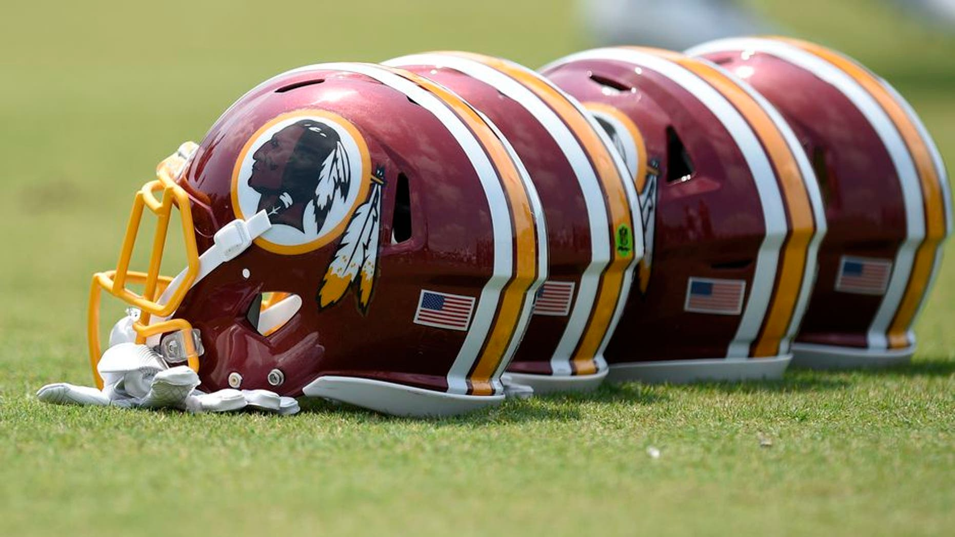Washington Redskins football helmets sit on the field during an NFL football team practice, Wednesday, June 14, 2017, in Ashburn, Va. (AP Photo/Nick Wass)