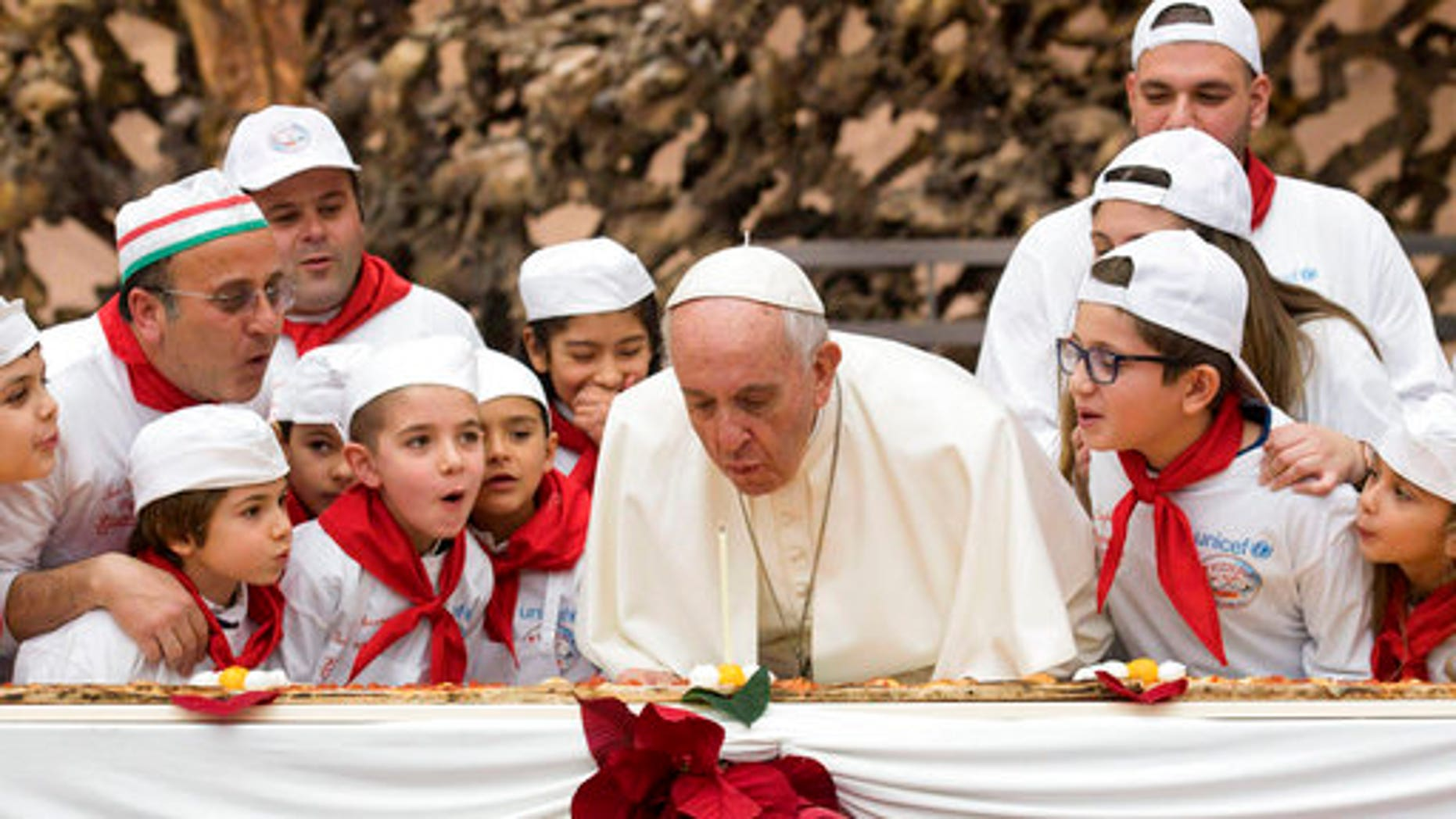 Pope Francis blows out a candle on pizza to celebrate his 81st birthday during a private audience with children at the Vatican.