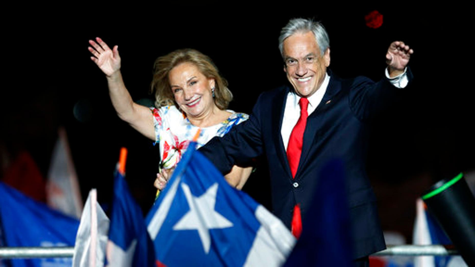 Chile's former President Sebastian Pinera and his wife Cecilia Morel wave to supporters as they celebrate Pinera's winning the presidential election runoff in Santiago, Chile.