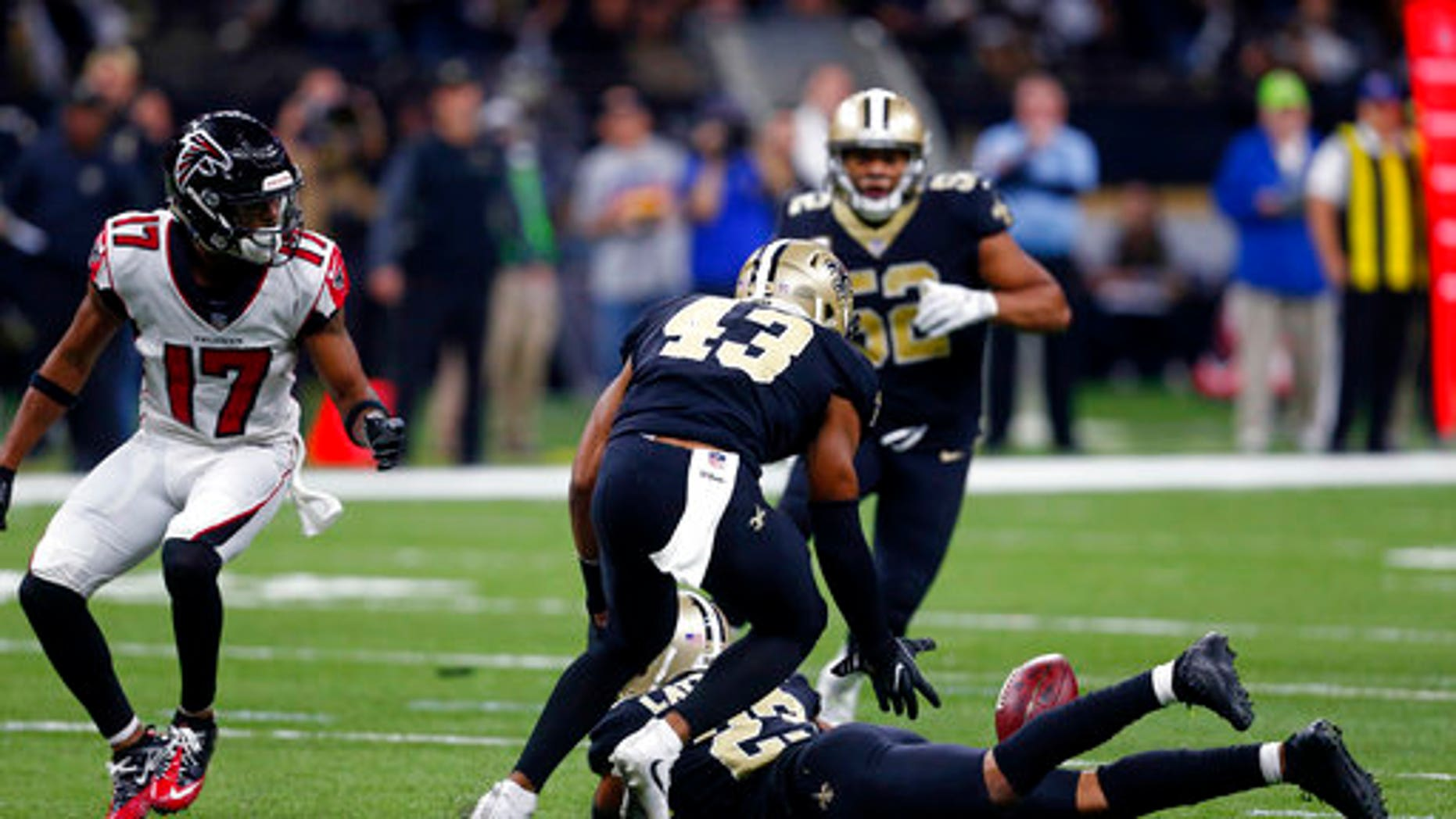 New Orleans Saints free safety Marcus Williams (43) scoops up an interception as the ball lands on the back of cornerback Marshon Lattimore.