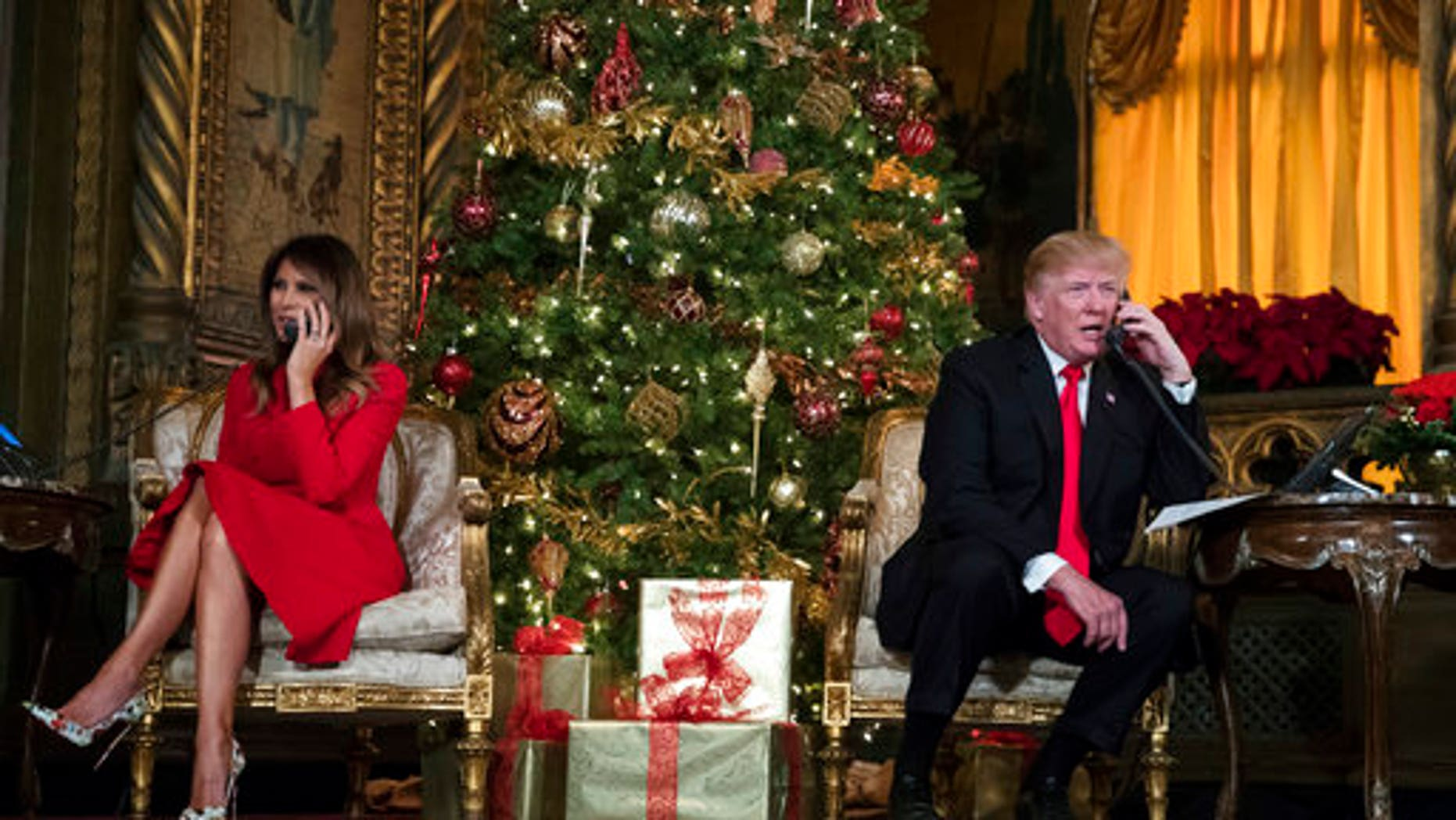President Donald Trump and first lady Melania Trump speak on the phone with children at the president's Mar-a-Lago estate in Palm Beach, Fla., Sunday, Dec. 24, 2017.