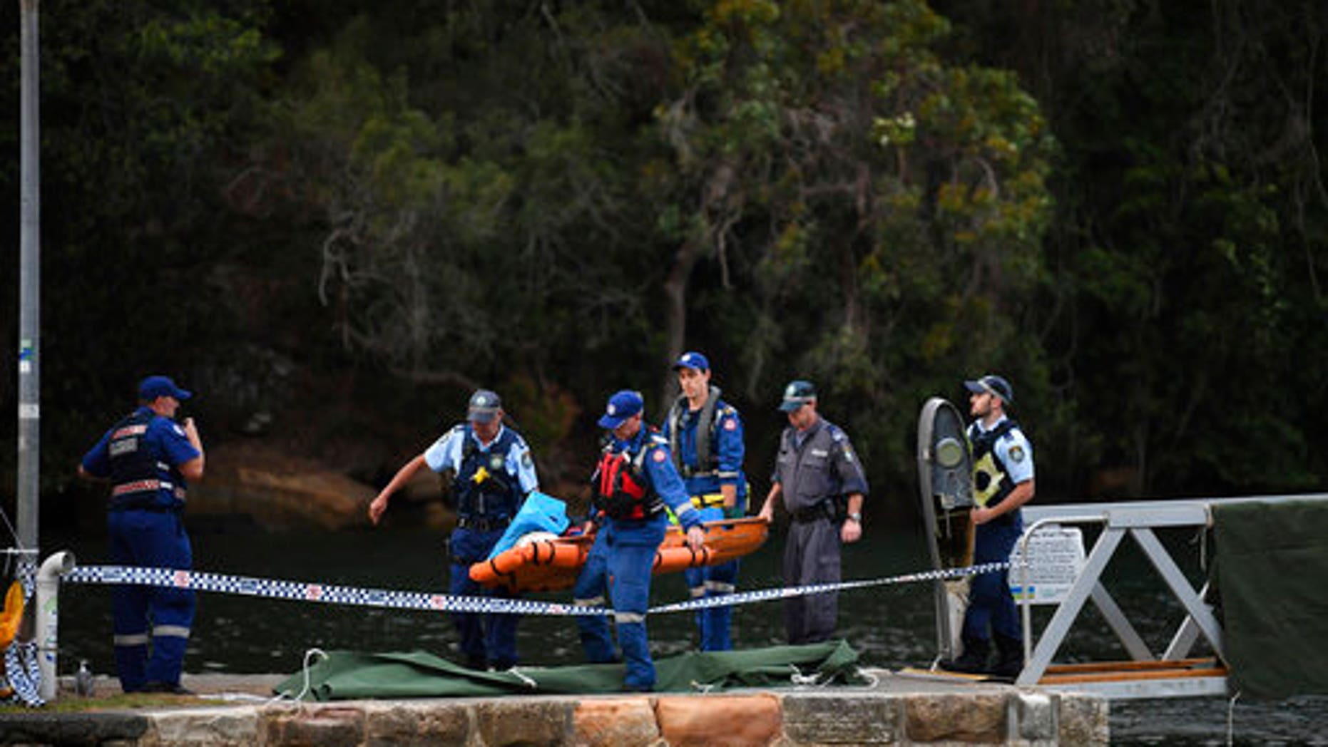 Emergency workers carry to shore what is believed to be a body and debris from a seaplane that crashed into the Hawkesbury River, north of Sydney, Australia.