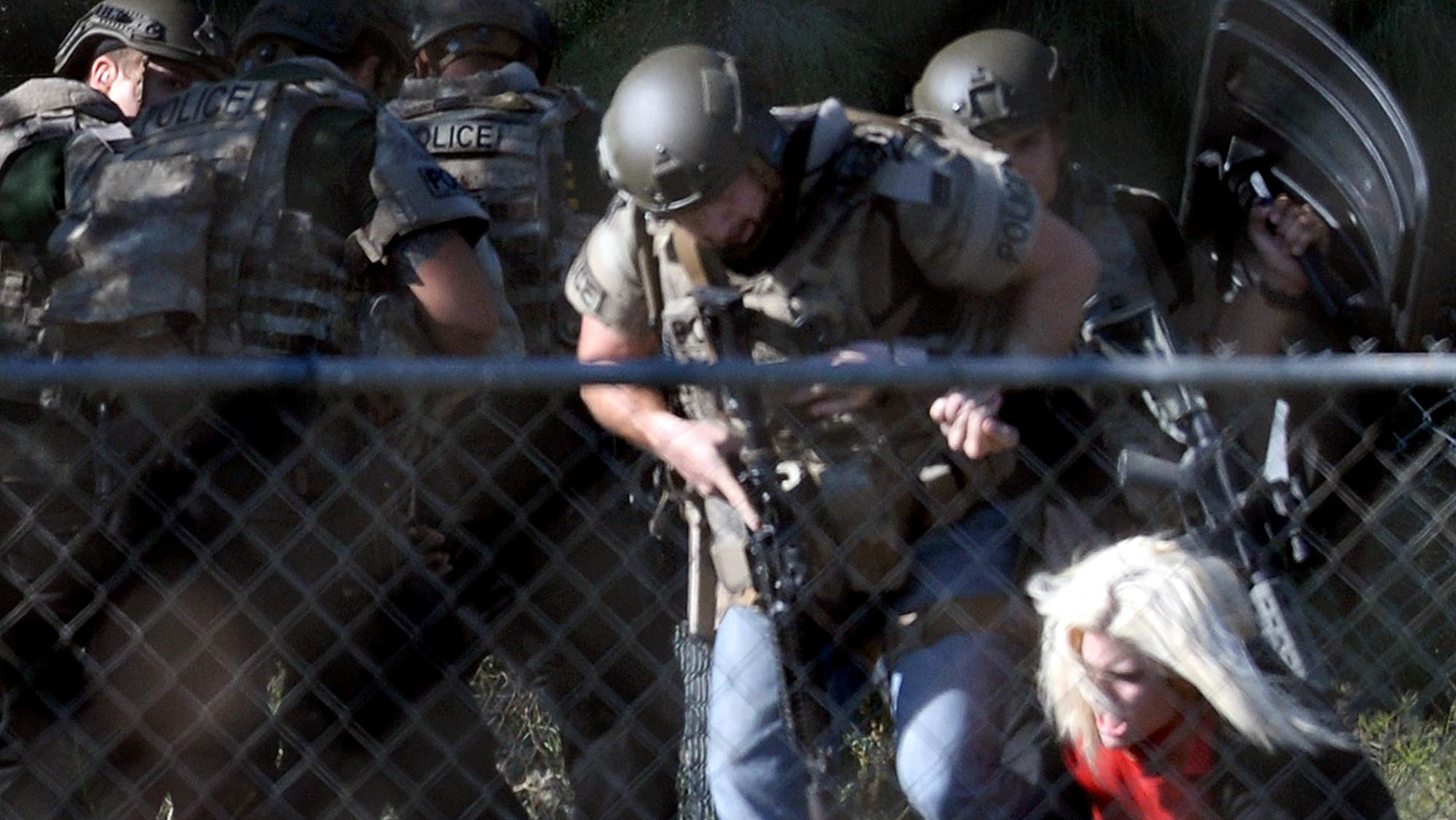 Police officers escort Kristin Bauer after the hostage-taking.