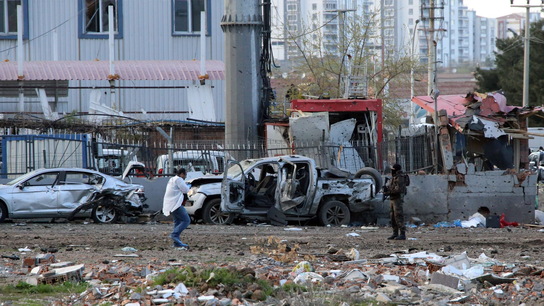Security and forensic officials work at the site after an explosion caused by a bomb-laden car targeting police in the mainly Kurdish city of Diyarbakir, Turkey, Thursday, March 31, 2016, Turkish news agencies reported.  The explosives detonated as a vehicle carrying special forces and riot police passed by, causing many deaths and injuries. (AP Photo/Mahmut Bozarslan)
