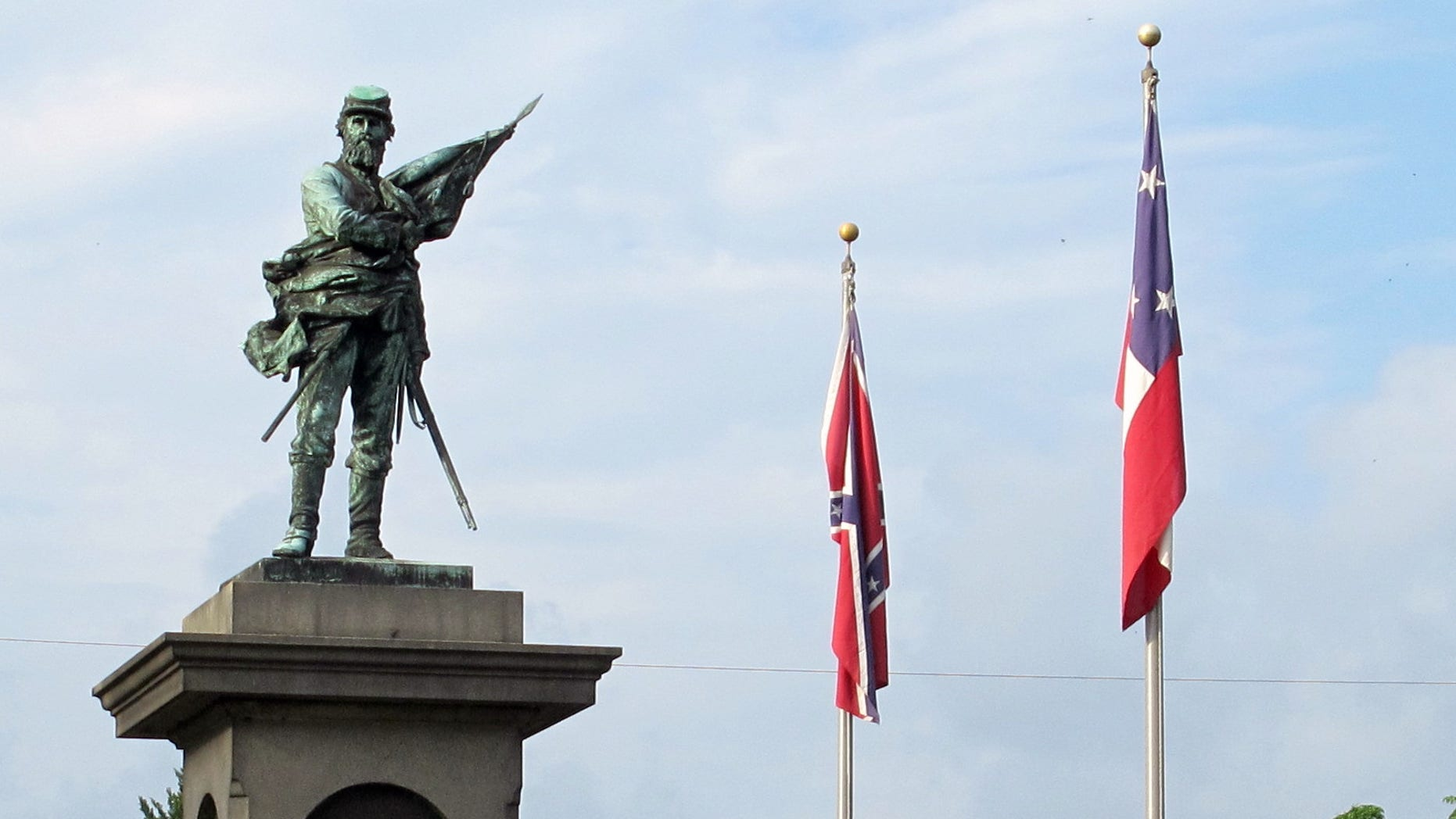 """Confederate flags fly near a monument at Magnolia Cemetery in Charleston., S.C., on Tuesday, May 10, 2016. On this day in 1863, Confederate Gen. Thomas """"Stonewall"""" Jackson died.  May 10 is observed as Confederate Memorial Day in the Carolinas.  (AP Photo/Bruce Smith)"""
