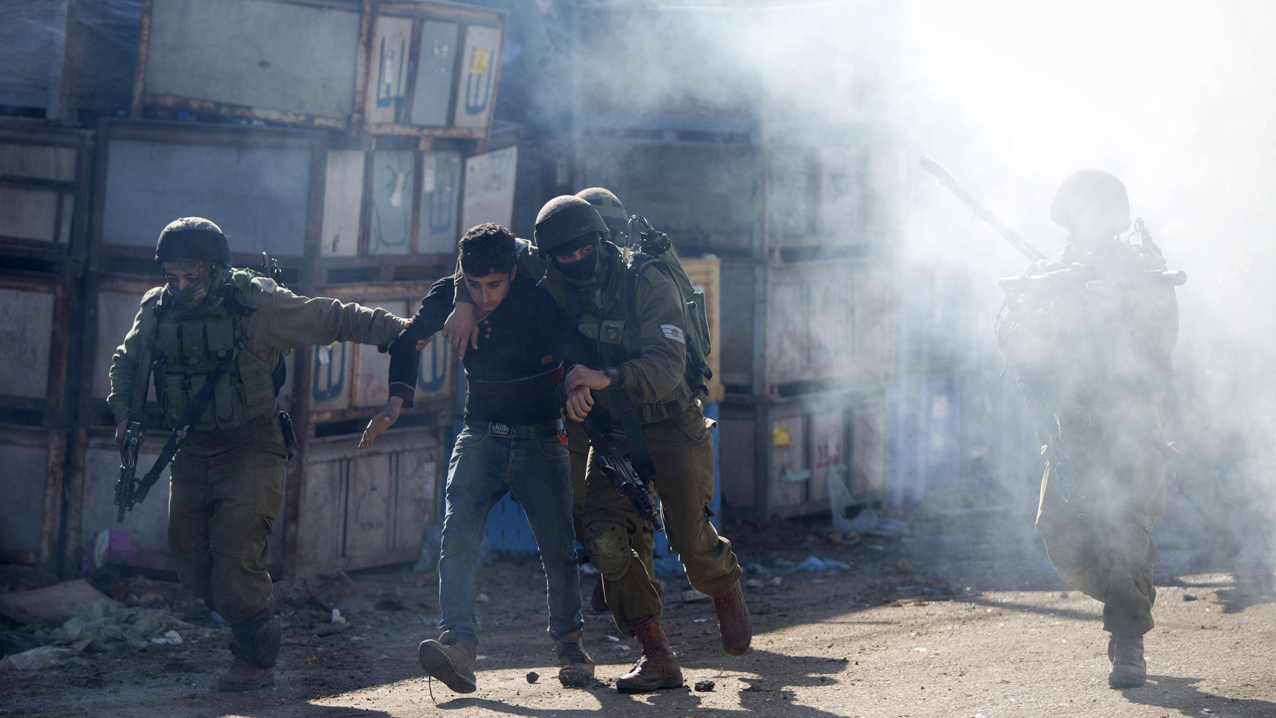 Israeli soldiers arrest a Palestinian protester during clashes in the West Bank village of Kabatiya Thursday.