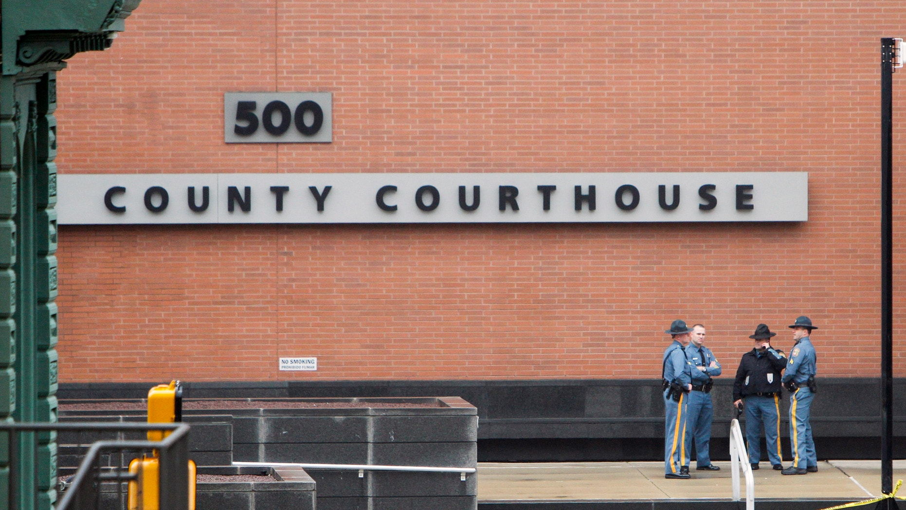 Law enforcement officials and investigators gather outside the New Castle County Courthouse in Wilmington, Del., in 2013.