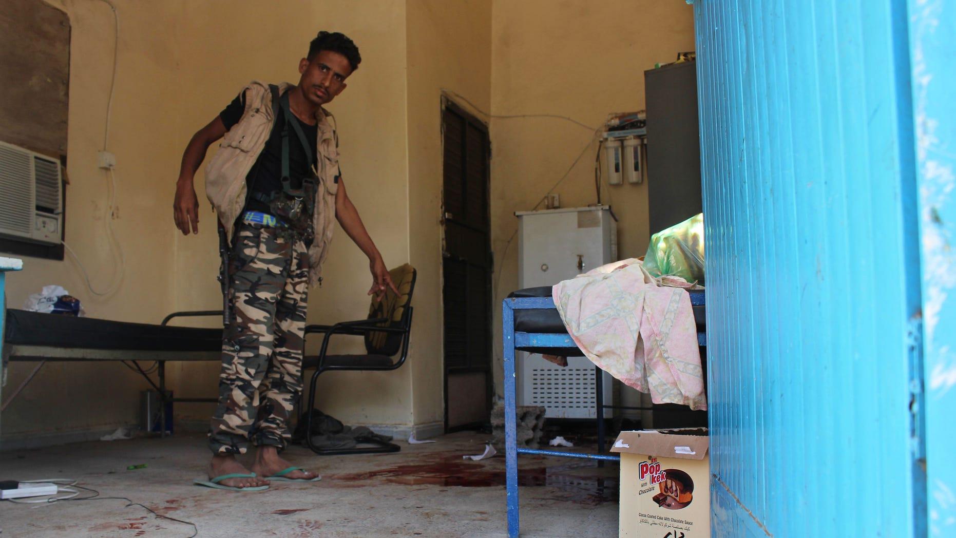 A Yemeni man inspects the scene of Friday's massacre.