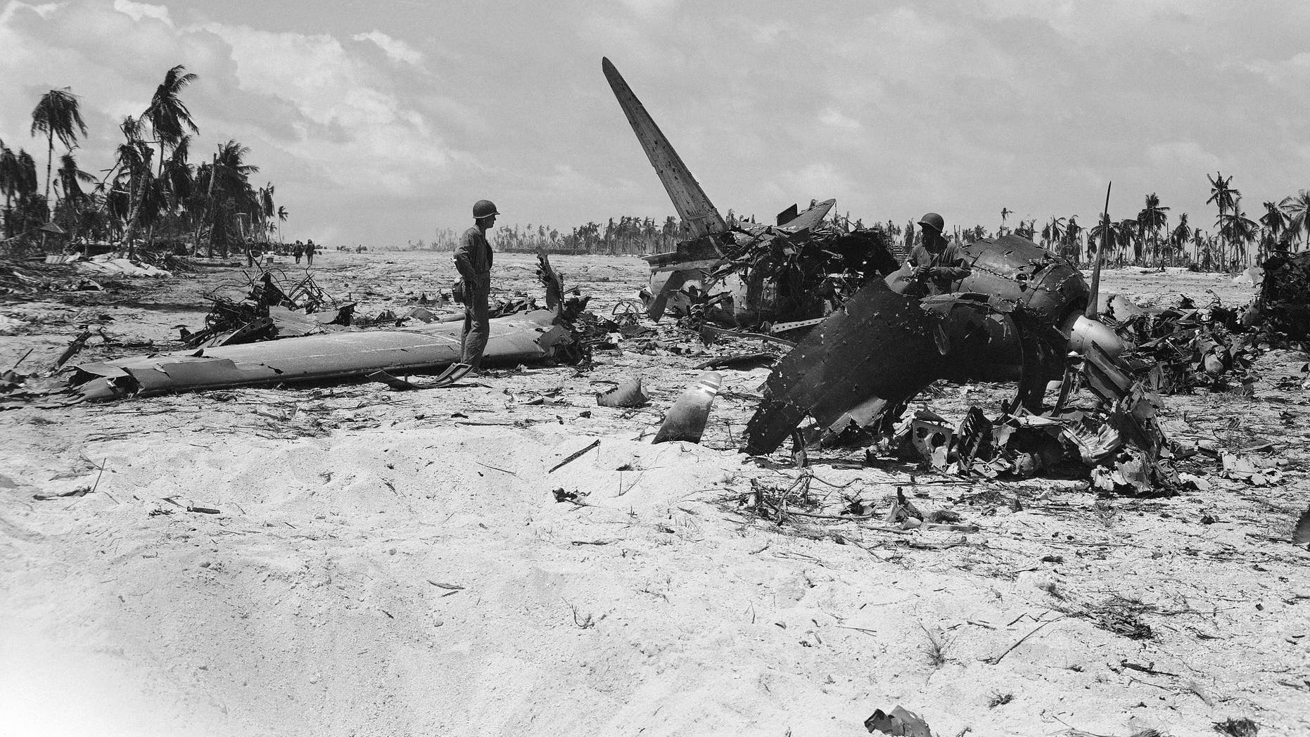 Marines examining the shattered wreckage of Japanese planes on the Tarawa Island airstrip in Tarawa Island on Dec. 1, 1943 after U.S. Marines battled their way ashore on Nov. 20. (AP Photo/Frank Filan)