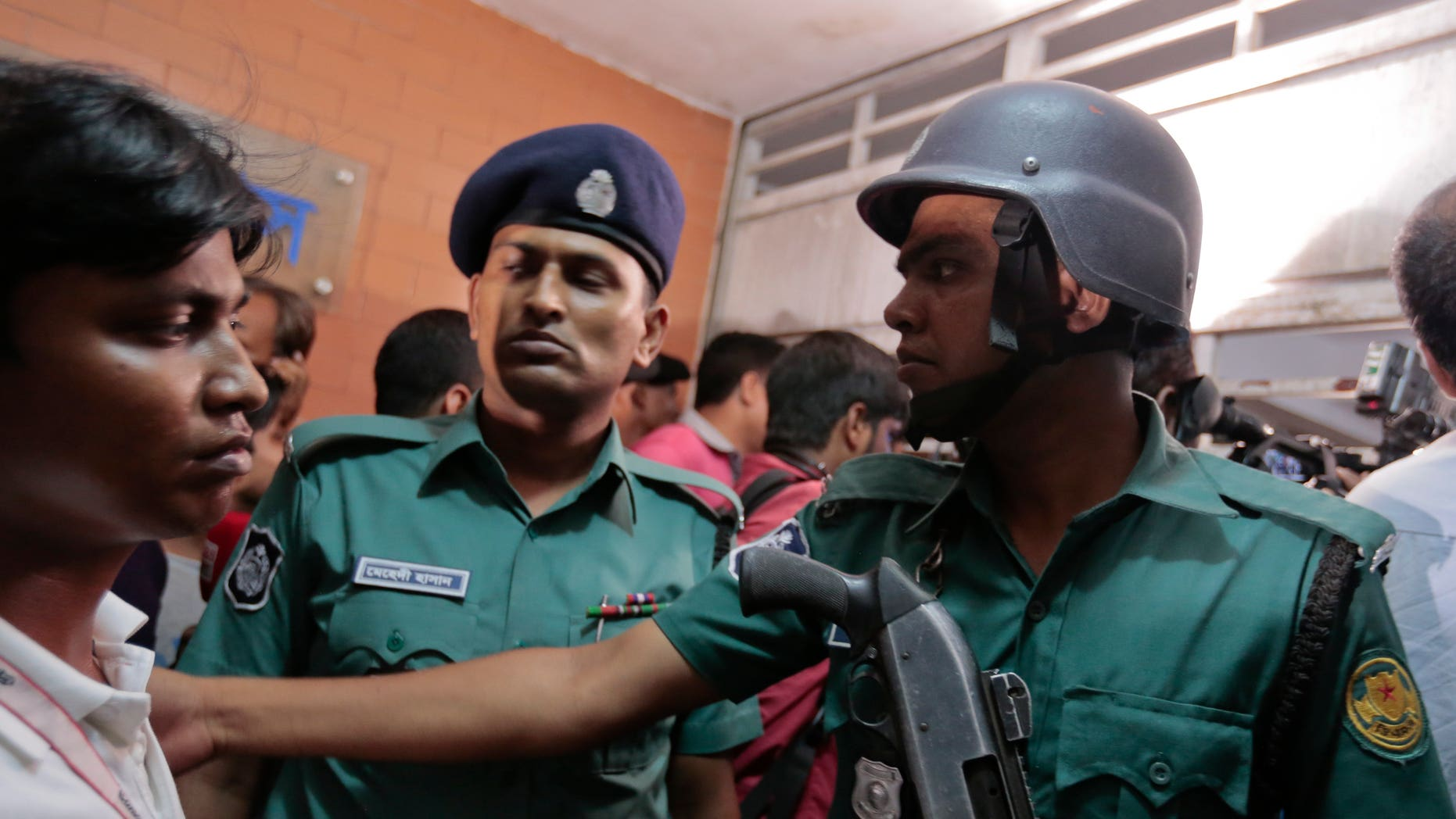 Bangladeshi policemen try to control the crowd of onlookers at a building in Dhaka where two people were found stabbed to death.