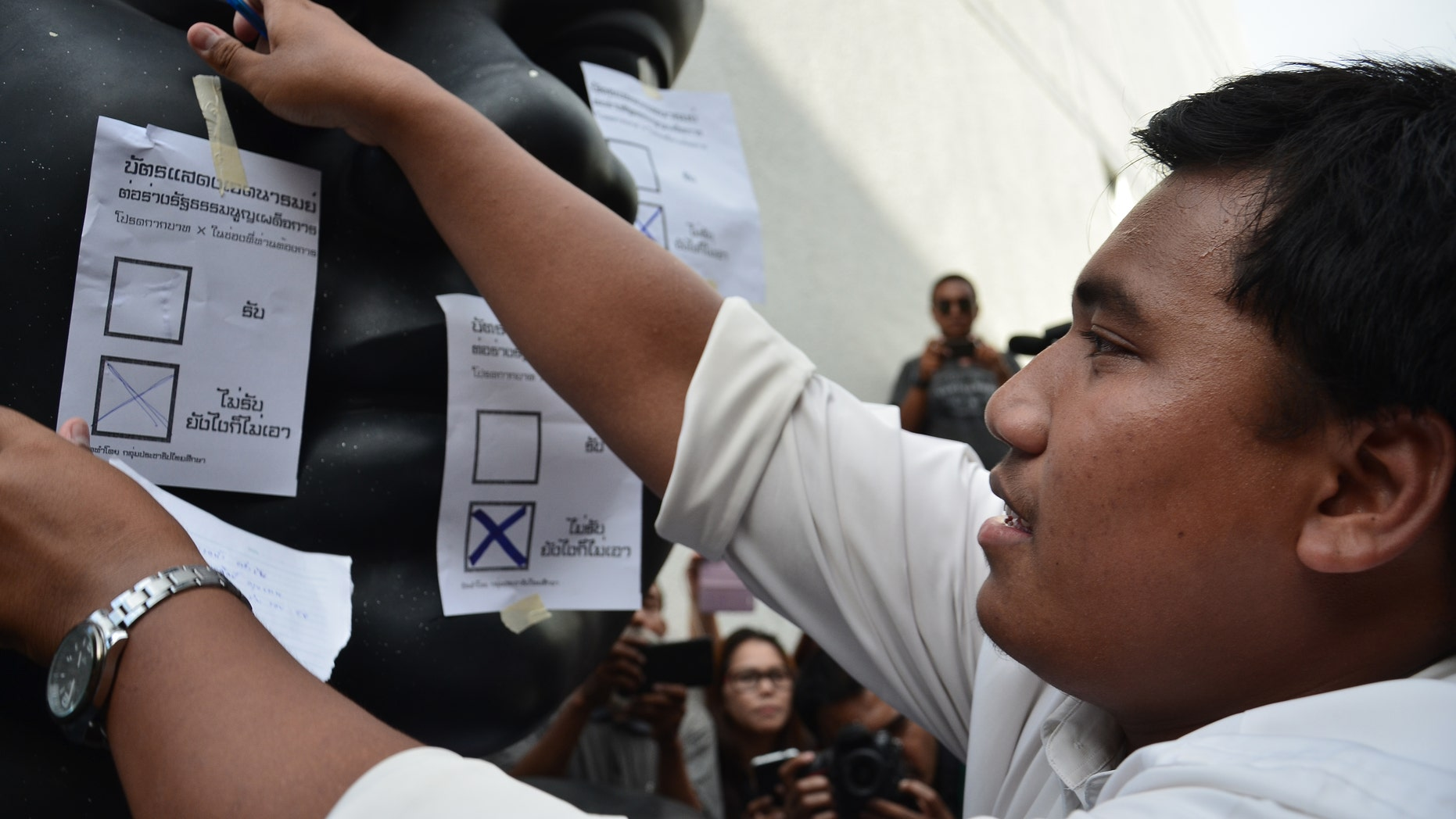 Sirawith Seritiwat sticks a mock ballot with 'NO' selected on a statue during a protest against a military-backed draft constitution, in September 2015.