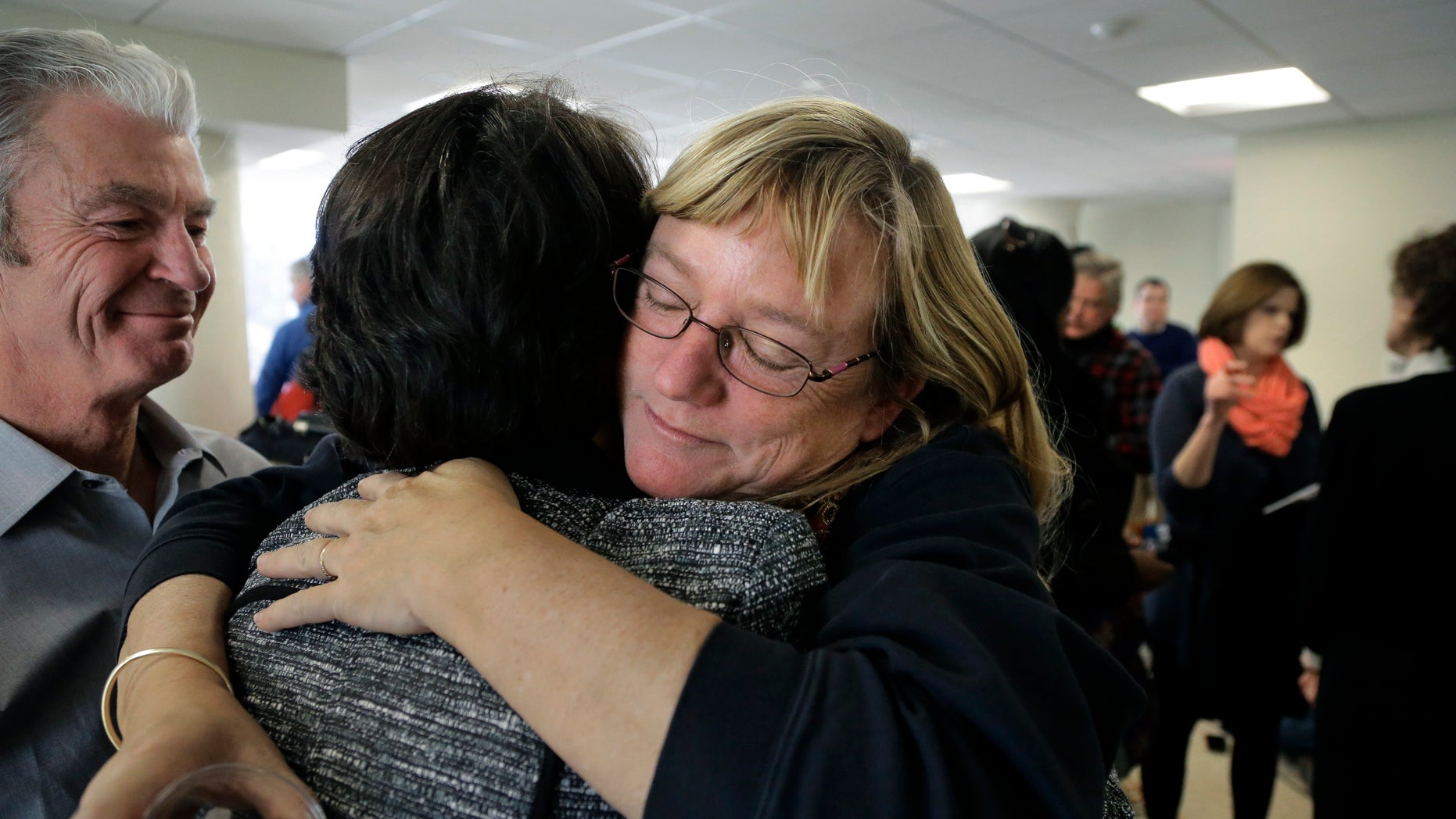 Katie Wales Lovkay, of Granby, Conn., right, who attended St. George's School from 1977-1980, hugs a former classmate, following a news conference, Tuesday, Jan. 5, 2016, in Boston. Former students of the prestigious boarding school in Middletown, R.I., are calling for an independent investigation into sexual abuse that they say spanned three decades and involved at least seven former staff members. Lovkay claims she was sexually assaulted by the school's now deceased athletic trainer. (AP Photo/Steven Senne)