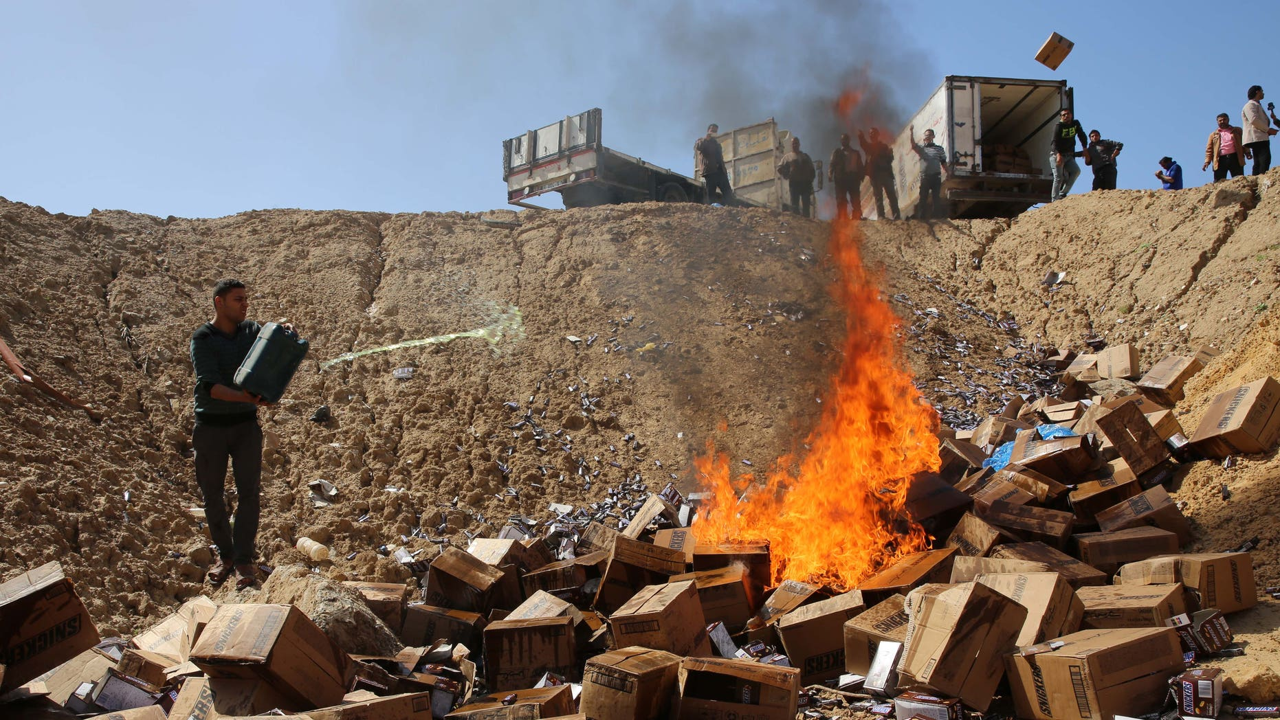 Palestinian worker throws gasoline on buringing boxes of Snickers chocolate on the outskirts of Gaza City, Thursday, March 10, 2016. Hamas authorities in Gaza say they disposed of 15 tons of chocolate in response to a mass recall the manufacturing company issued last month. (AP Photo/Adel Hana)