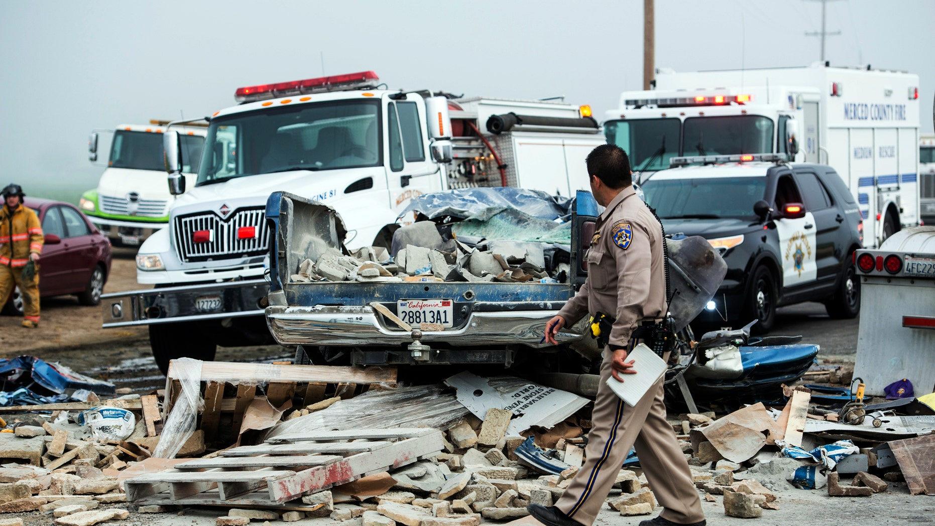 Emergency personnel work at the scene of a crash, one of several separate collisions, on Highway 59 in Merced County, Calif., Saturday, Feb. 13, 2016. The CHP says there was fog on the highway around the time of the crashes, but the cause remains under investigation. (Andrew Kuhn/Merced Sun-Star via AP)