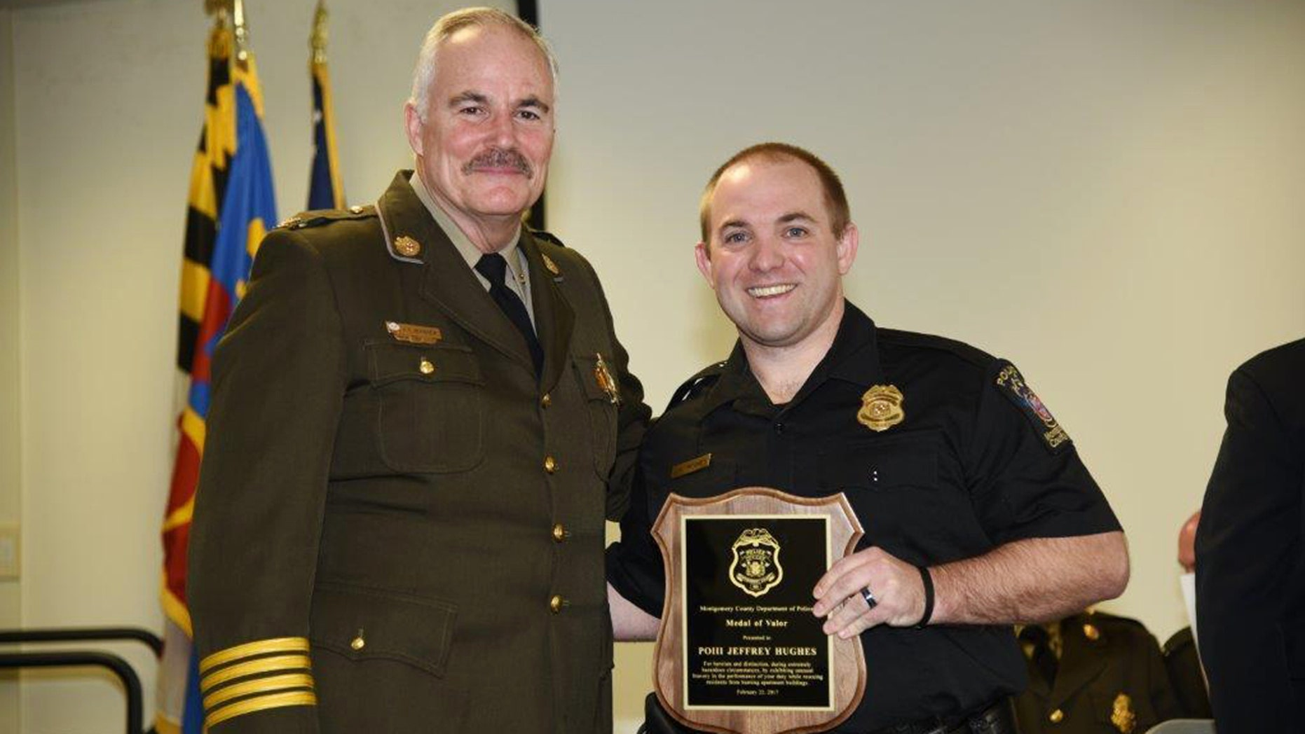 In this Feb. 22, 2017 photo provided by Montgomery County Police, Officer Jeff Hughes, right, poses for a photo with the Medal of Valor award with Chief Tom Manger in Gaithersburg, Md.