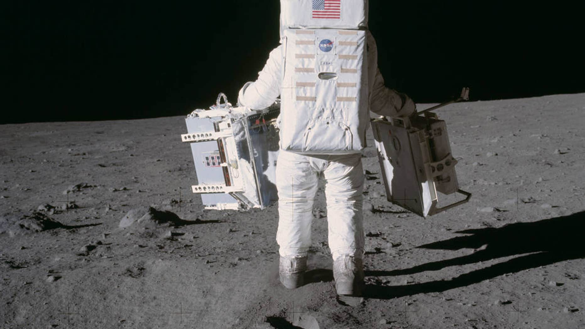 Buzz Aldrin on the moon, carrying two scientific instruments.